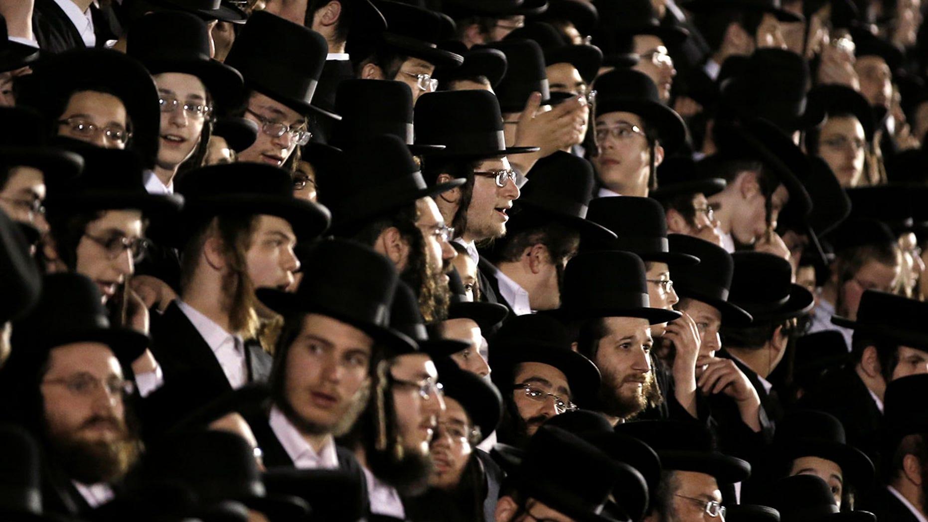 Orthodox Jews of the Satmar Hasidim crowd bleachers near a bonfire in the New York village of Kiryas Joel.