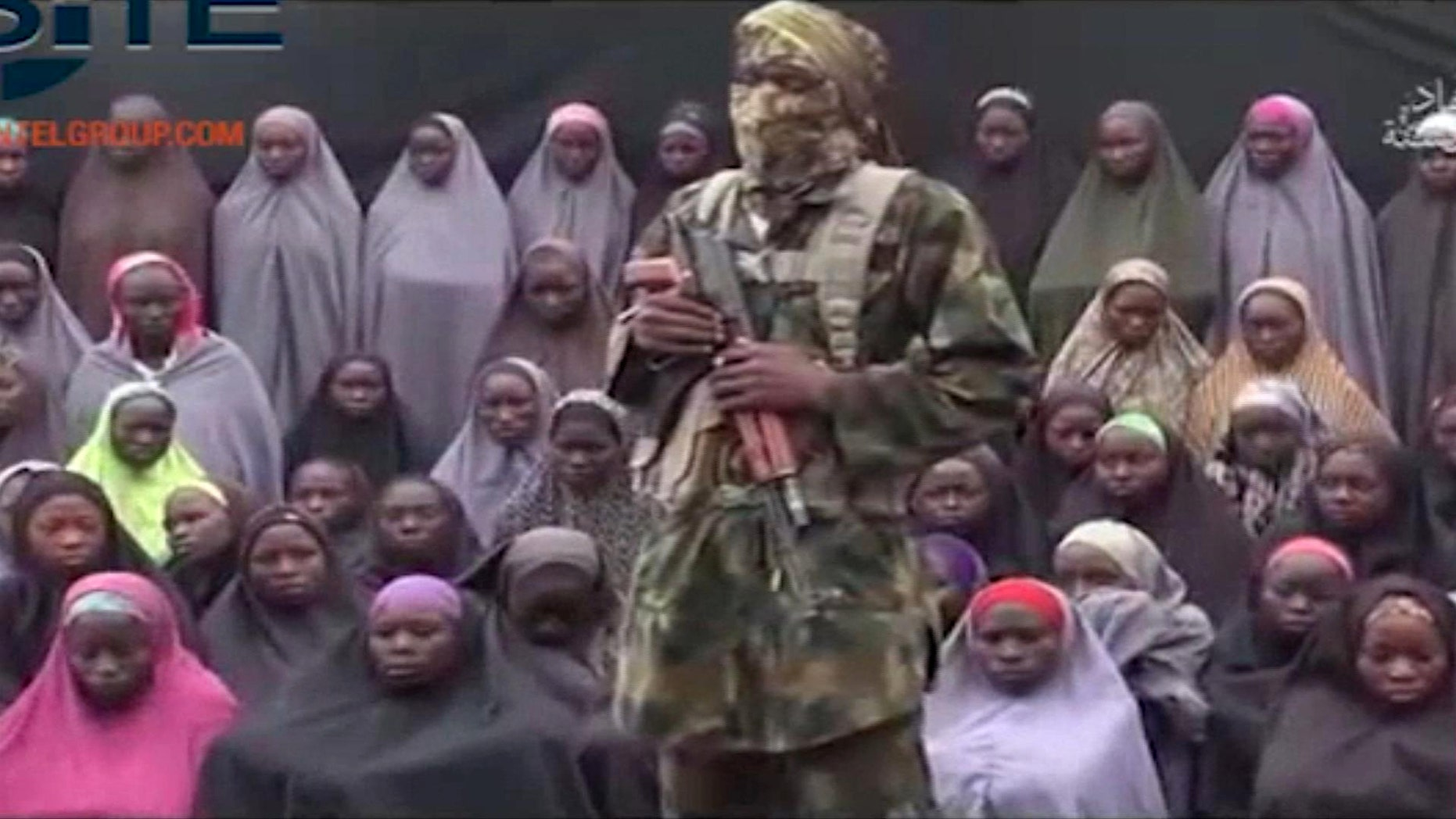An alleged Boko Haram soldier stands in front of a group of girls alleged to be some of the 276 abducted Chibok schoolgirls held since April 2014, in an unknown location, in video distributed in August 2016.