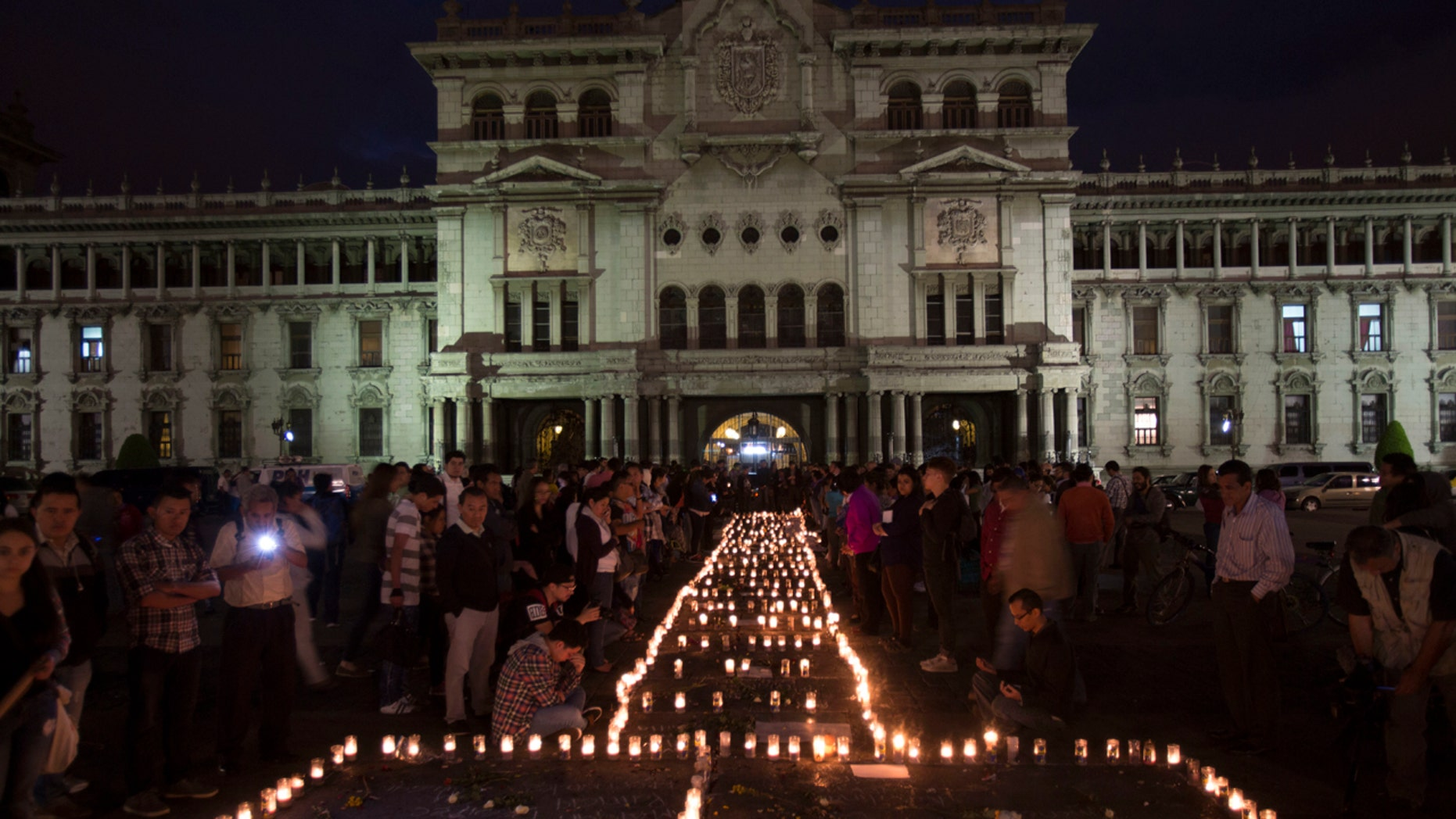 People hold a candlelight vigil outside the National Palace in remembrance of the girls who died in a fire at the Virgin of the Assumption Safe Home in Guatemala City, Thursday, March 9, 2017.