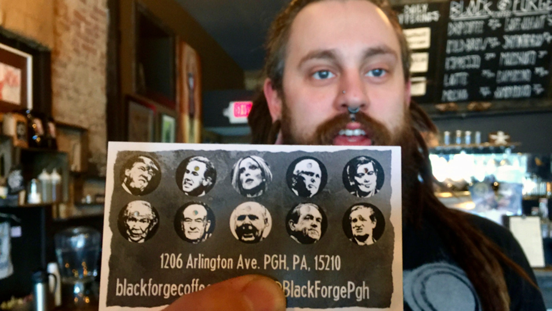 In this Thursday, March 30, 2017 photo, Nick Miller, co-owner of the Black Forge Coffee House in Pittsburgh's Allentown neighborhood, holds a punch card featuring President Donald Trump and nine other conservative politicians and media icons. The card has caused a mini-furor with the shop receiving a deluge of phone calls and online comments, both of disparagement and support from around the country.  Miller says the satiric cards are meant to express frustration with the system and nothing more. (Dan Gigler /Pittsburgh Post-Gazette via AP)