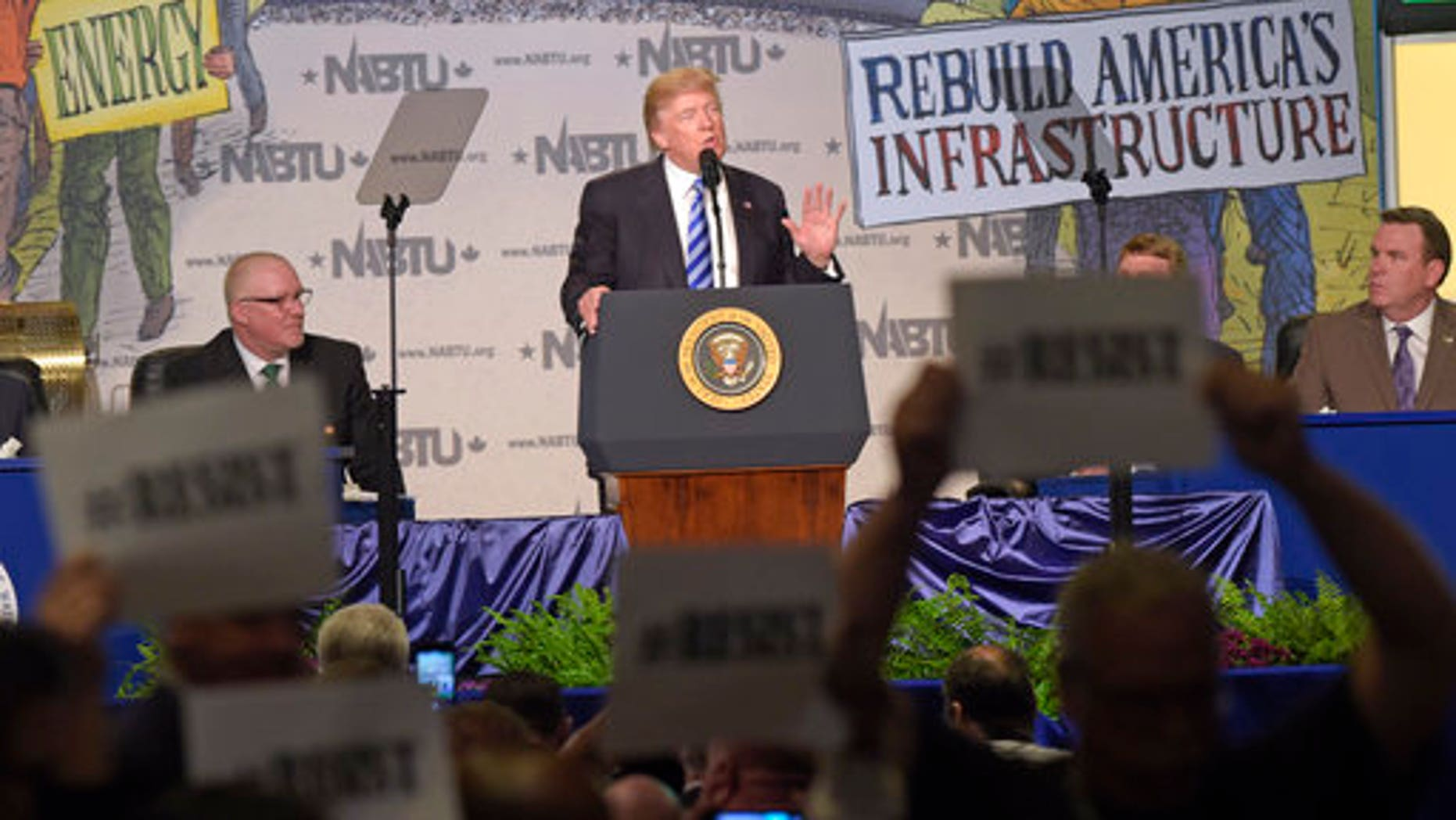 Protesters hold up signs as President Donald Trump speaks at the 2017 North America's Building Trades Unions National Legislative Conference in Washington, Tuesday, April 4, 2017. (AP Photo/Susan Walsh)