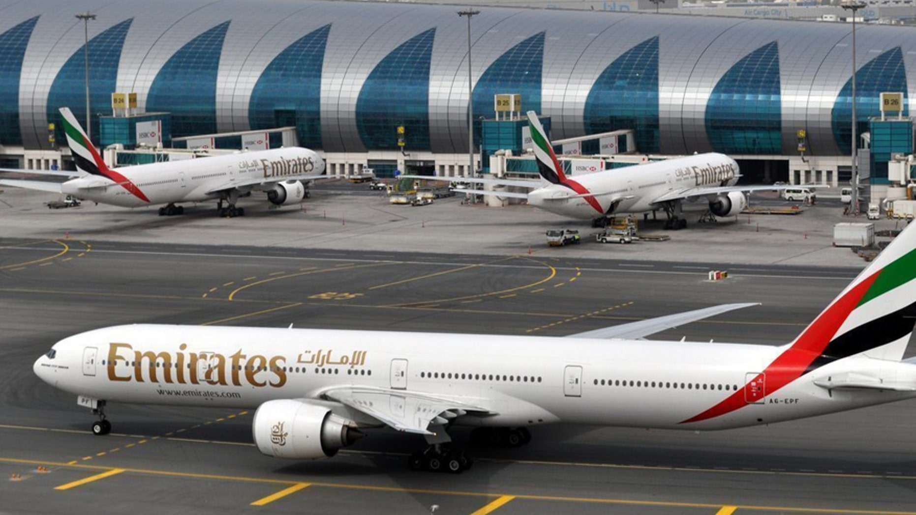 FILE- In this Wednesday, March 22, 2017 file photo, an Emirates plane taxis to a gate at Dubai International Airport at Dubai International Airport in Dubai, United Arab Emirates. The Middle East's biggest airline says it is reducing flights to the United States because of a drop in demand caused by tougher U.S. security measures and attempts by the Trump administration to ban travelers from a number of Muslim-majority nations. (AP Photo/Adam Schreck, File)