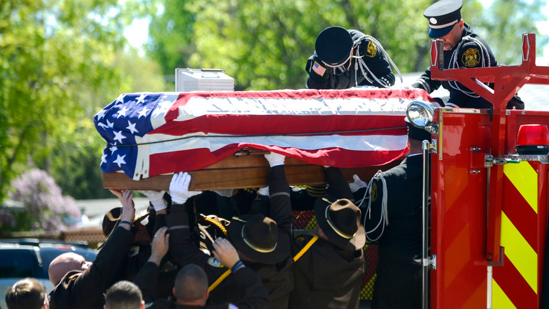 Law enforcement lift Deputy Mason Moore's casket down from a firetruck in front of Three Forks High School, the end of the funeral procession in Three Forks, Montana, on Tuesday.