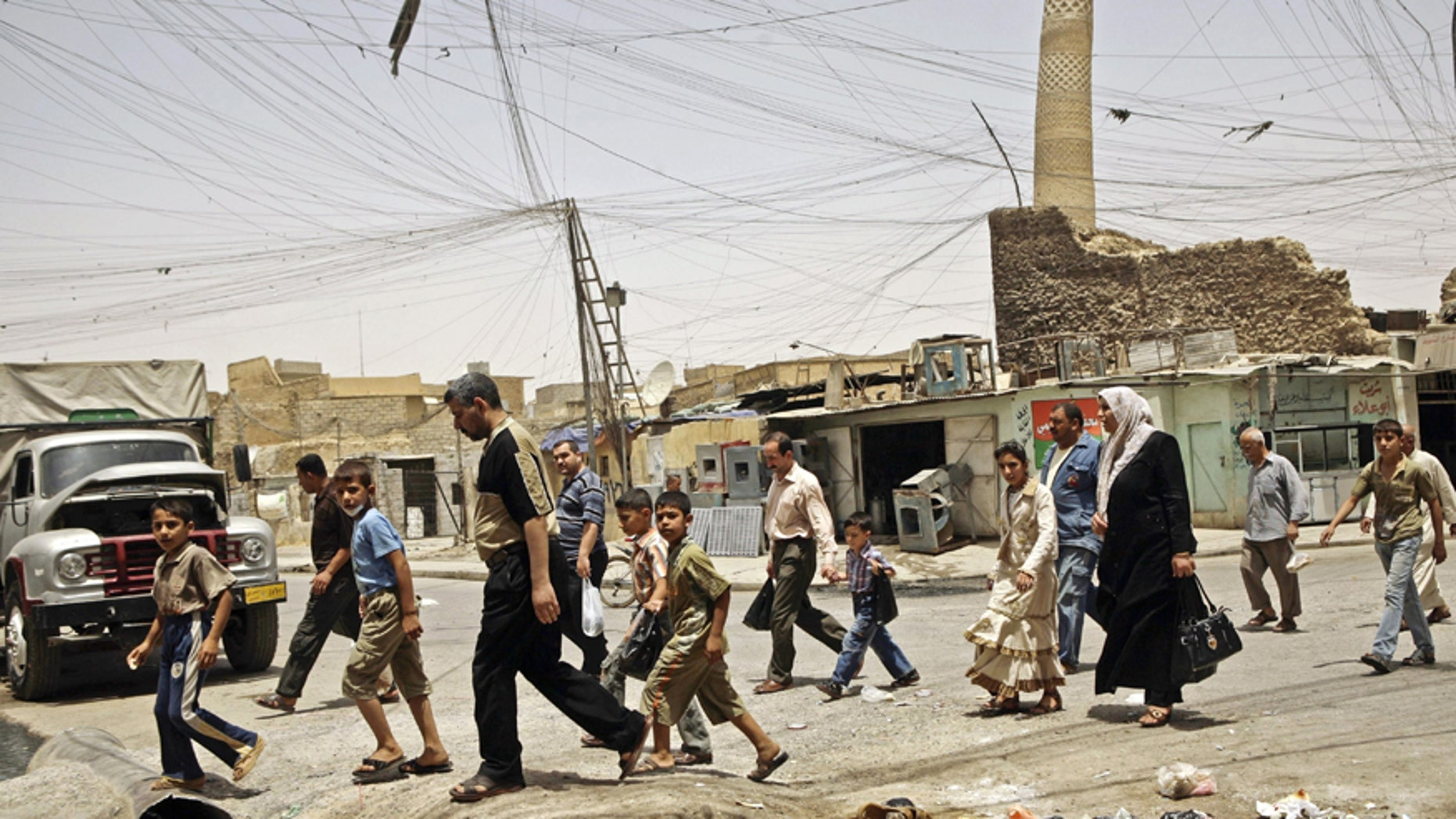 FILE -- In this June 8, 2009 file photo, residents walk past the tilted minaret of al-Nuri mosque — also known as the Great Mosque — in Mosul, Iraq. A resident in the Islamic State-held Mosul's Old City says the militants have blocked the area around the highly symbolic mosque where the group's leader Abu Bakr al-Baghdadi made his first and only public appearance. (AP Photo/Maya Alleruzzo, File)