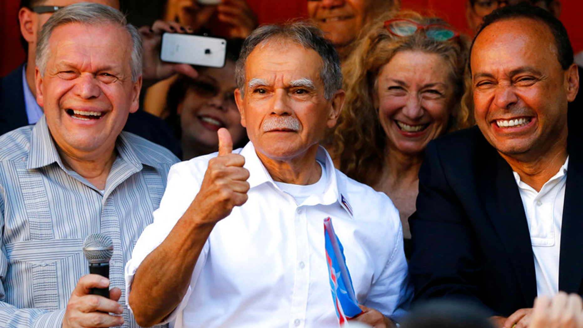 FILE- In this May 18, 2017 file photo, Puerto Rican nationalist Oscar Lopez Rivera, center, reacts to the crowd as his brother Jose, left, and U.S. Rep Luis Gutierrez, D-Ill., join him at a gathering in his honor in Chicago's Humboldt Park neighborhood. New York City's annual Puerto Rican Day parade will take place under a cloud of controversy this year because of a decision by organizers to honor Lopez Rivera, who spent decades in prison because of his involvement with the terrorist group FALN. (AP Photo/Charles Rex Arbogast, File)