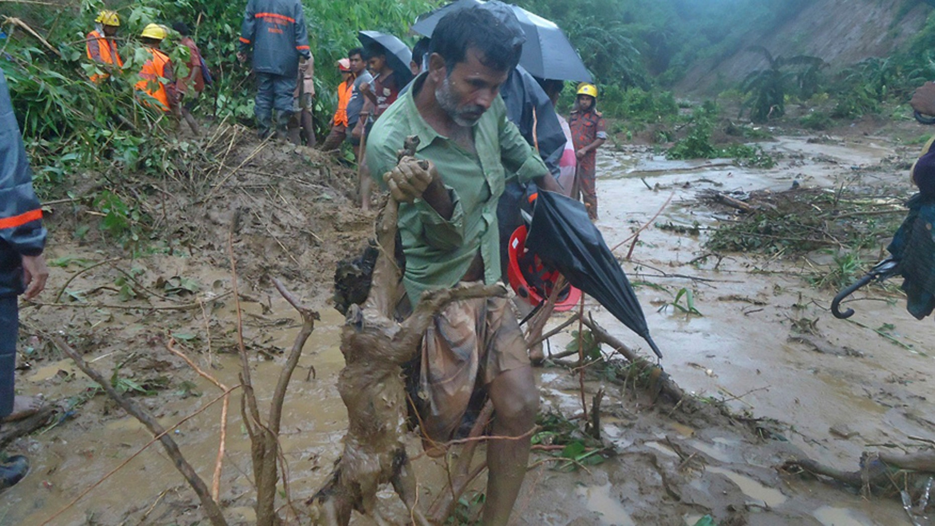 A man carries the carcass of a goat as rescuers search amid the mud after a landslide in Bandarban, Bangladesh, Tuesday, June 13, 2017. Heavy rains triggered landslides that killed dozens in southeast Bangladesh, officials said Tuesday, as police and soldiers struggled to reach the remote districts with aid. (AP Photo)
