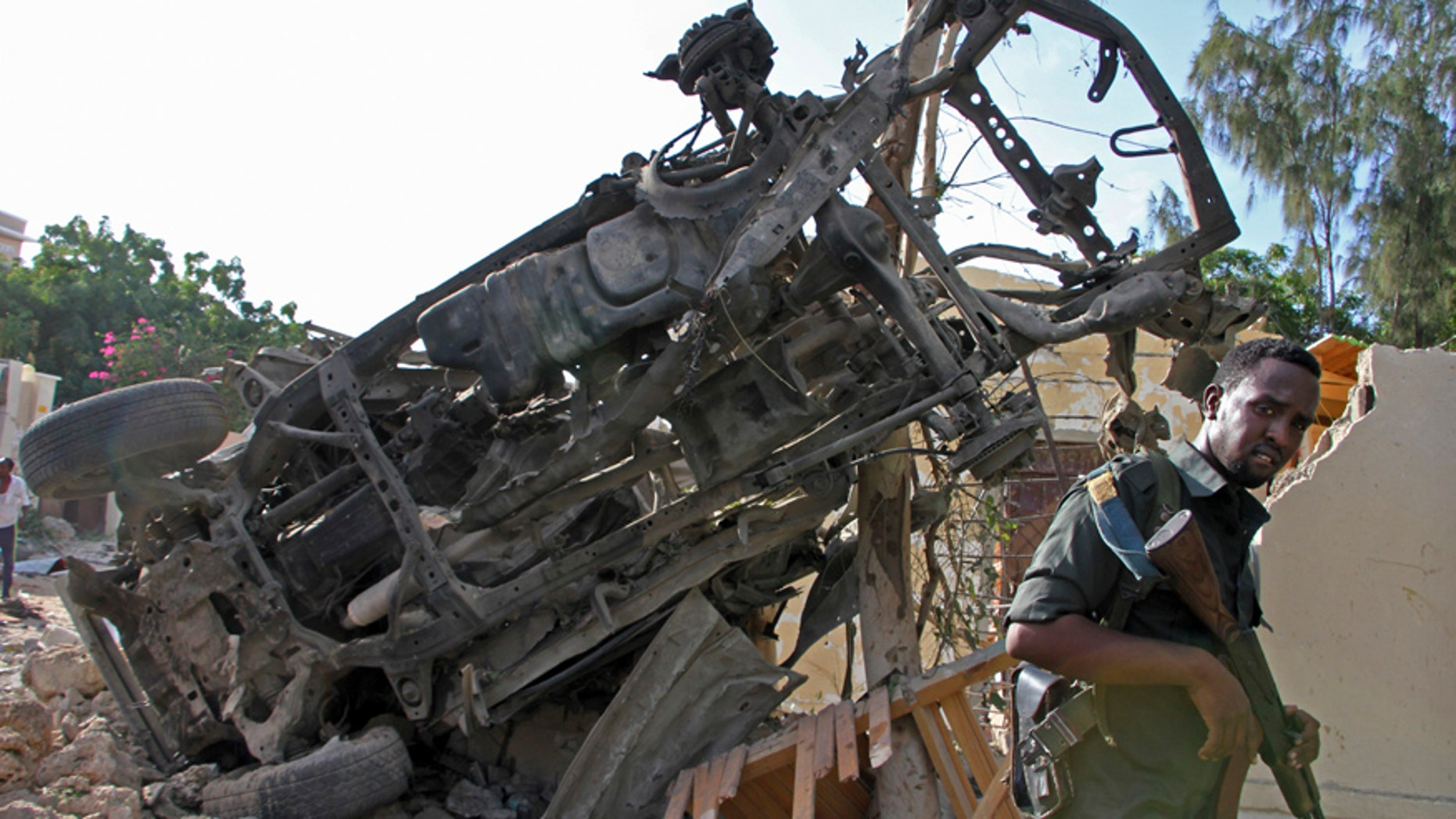 """A Somali soldier stands near the wreckage from a car bomb blast and gun battle targeting a restaurant in Mogadishu, Somalia, Thursday, June 15, 2017. Somalia's security forces early Thursday morning ended a night-long siege by al-Shabab Islamic extremists at the popular """"Pizza House"""" restaurant in the capital. (AP Photo/Farah Abdi Warsameh)"""