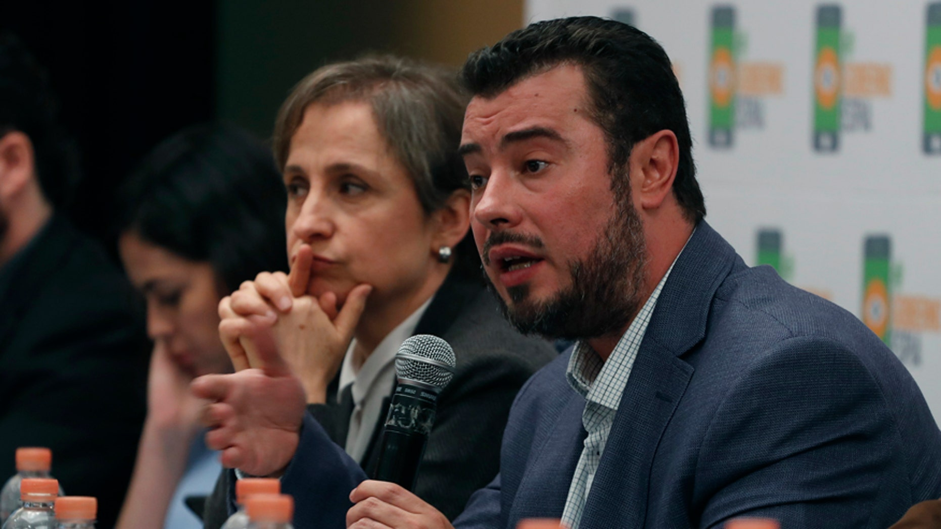 Mario Patron Sanchez, director of the Miguel Agustín Pro Juárez Center for Human Rights, talks during a news conference, seated next to Mexican journalist Carmen Aristegui, in Mexico City on Monday.