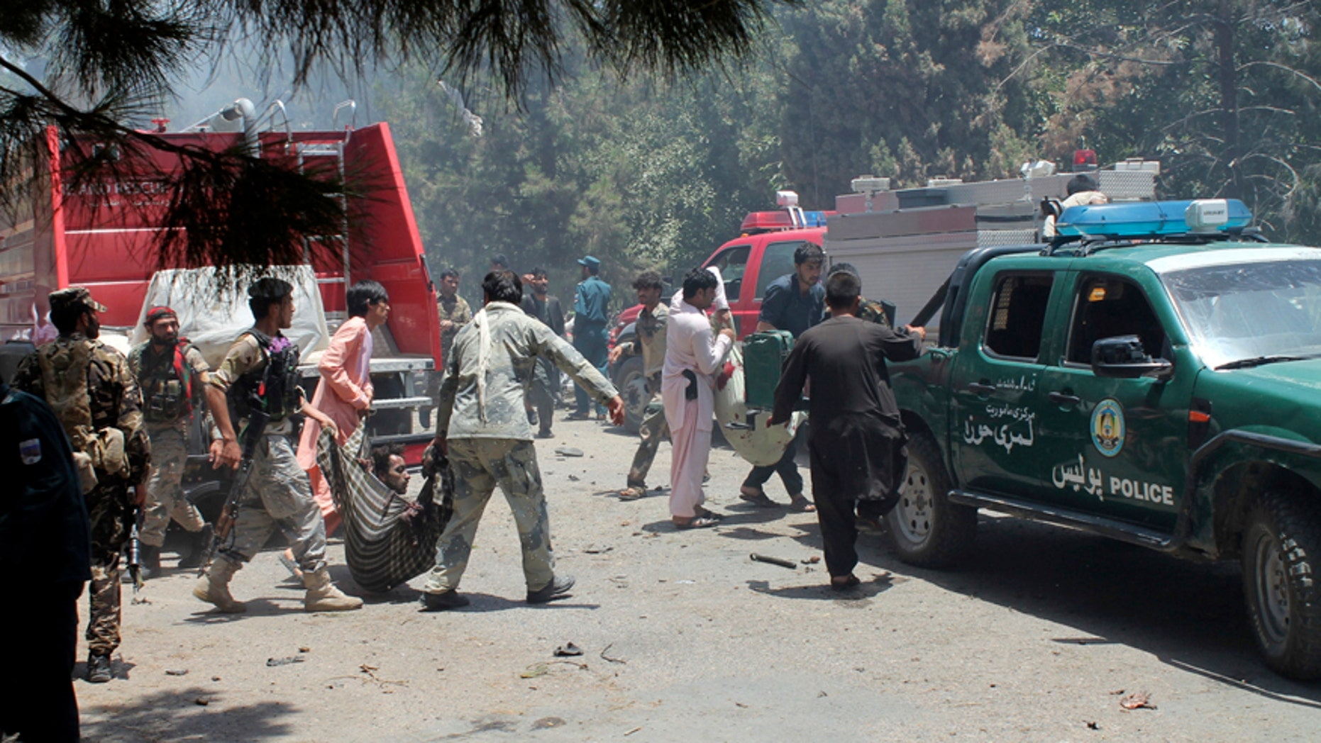 Afghans carry an injured man after a suicide car bombing in Helmand province southern of Kabul, Afghanistan, Thursday, June 22, 2017. The bomber struck outside a bank, targeting Afghan troops and government employees waiting to collect their salaries ahead of a major Muslim holiday and killing at least two dozen people, officials said. (AP Photo/Abdul Khaliq)