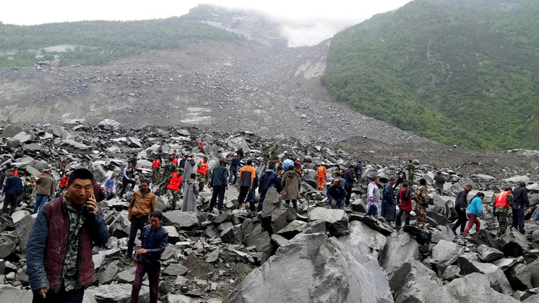 FILE: Emergency personnel work at the site of a landslide in Xinmo village in Maoxian County in southwestern China's Sichuan Province