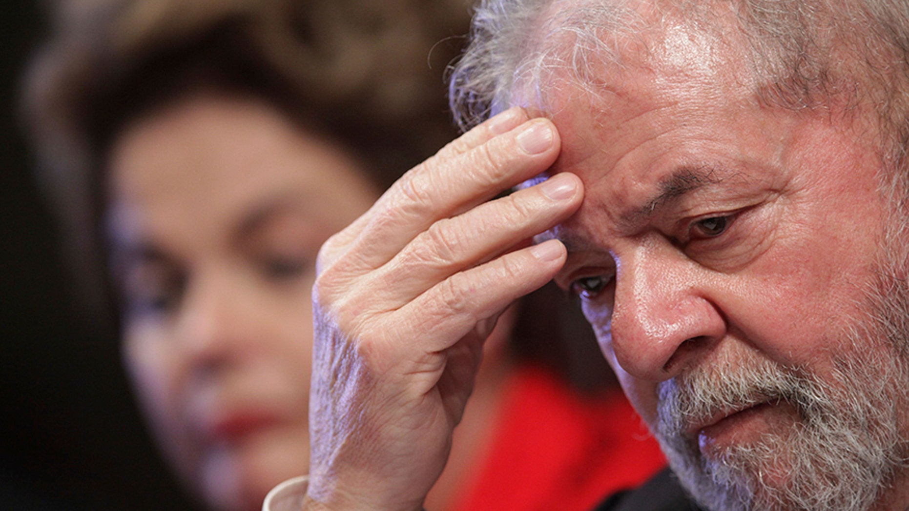 FILE - In this July 5, 2017 file photo, Brazil's Former President Luiz Inacio Lula da Silva attends the inauguration ceremony for the new leadership of the Workers' Party, with ousted President Dilma Rousseff, behind, in Brasilia, Brazil. A Brazilian federal judge has convicted the former president of corruption and money laundering on Wednesday, July 12, 2017. (AP Photo/Eraldo Peres, File)