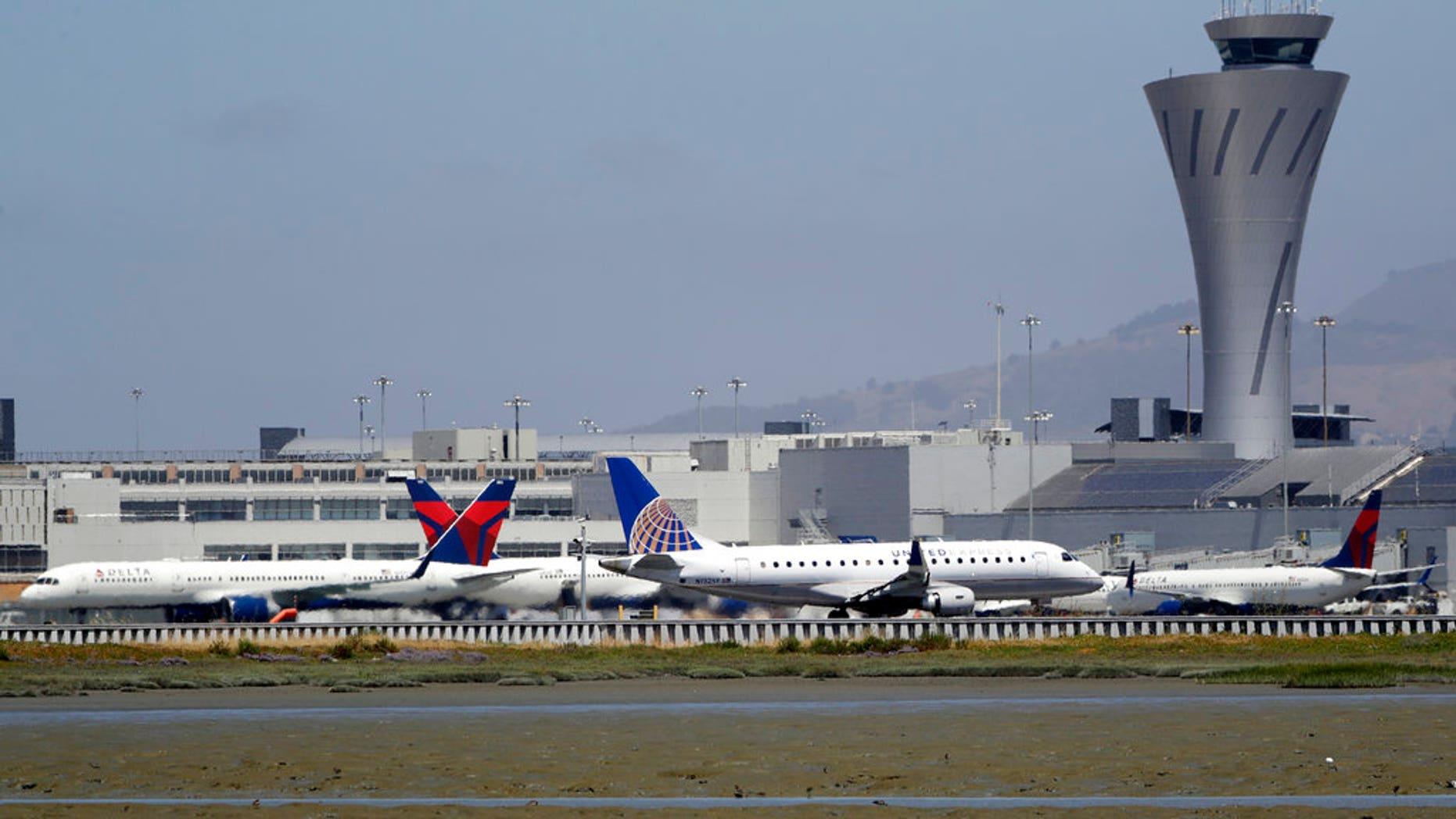 July 11, 2017: Departing and parked aircraft intersect at San Francisco International Airport.
