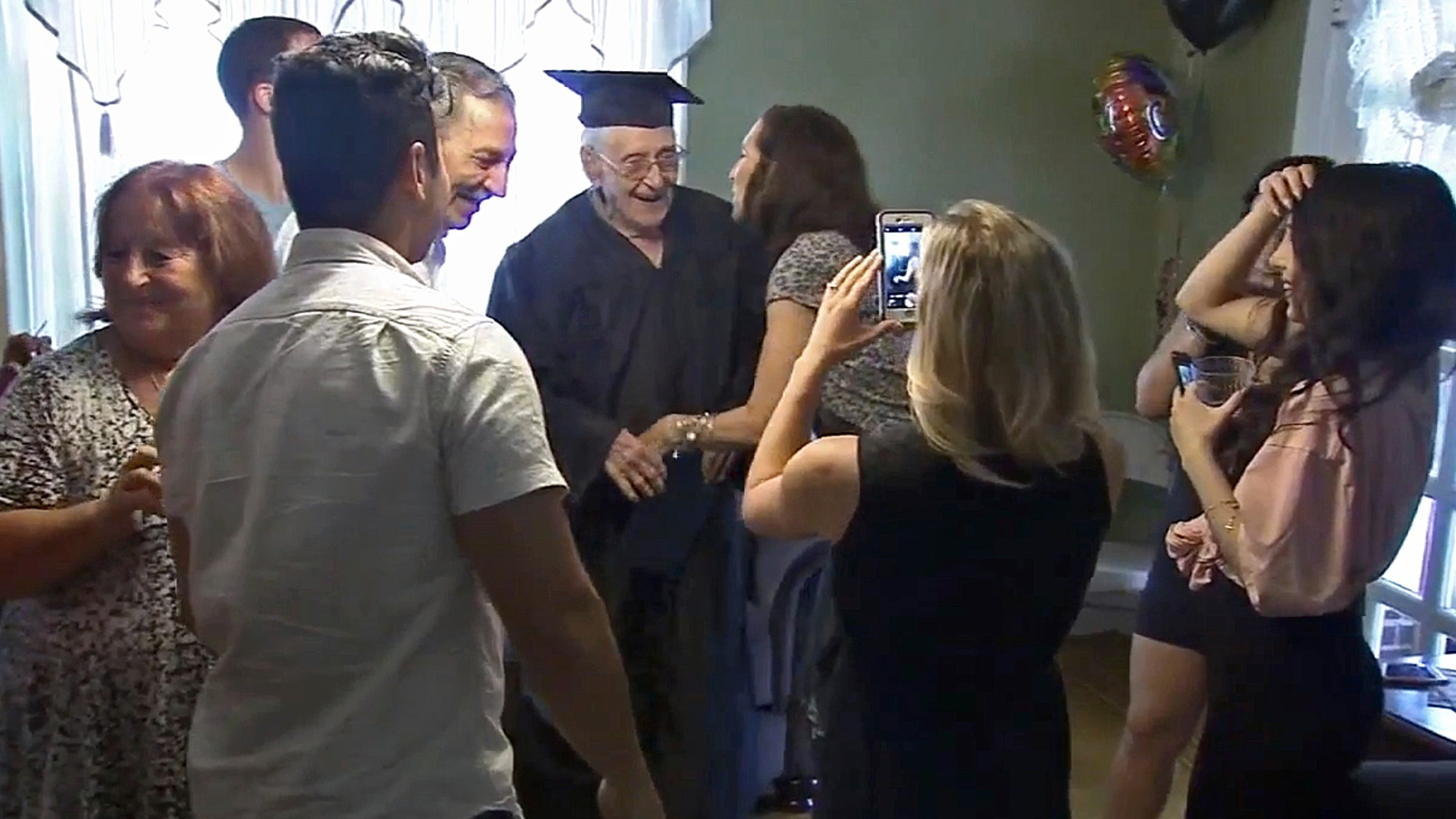Charles Leuzzi, center, a 97-year-old World War II veteran, is congratulated by friends and relatives after receiving an honorary high school diploma.