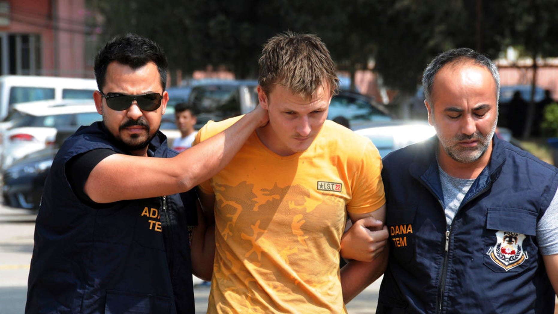 Turkish police walk with a handcuffed Renad Bakiev, center.