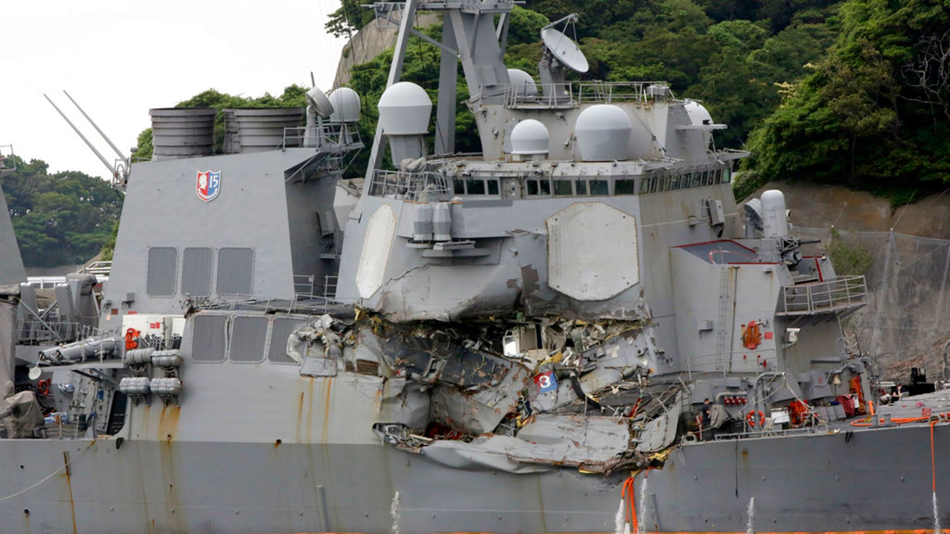 In this June 18, 2017, photo, damaged USS Fitzgerald is docked at the U.S. Naval base in Yokosuka, southwest of Tokyo, after colliding with Philippine-flagged container ship ACX Crystal off Japan.