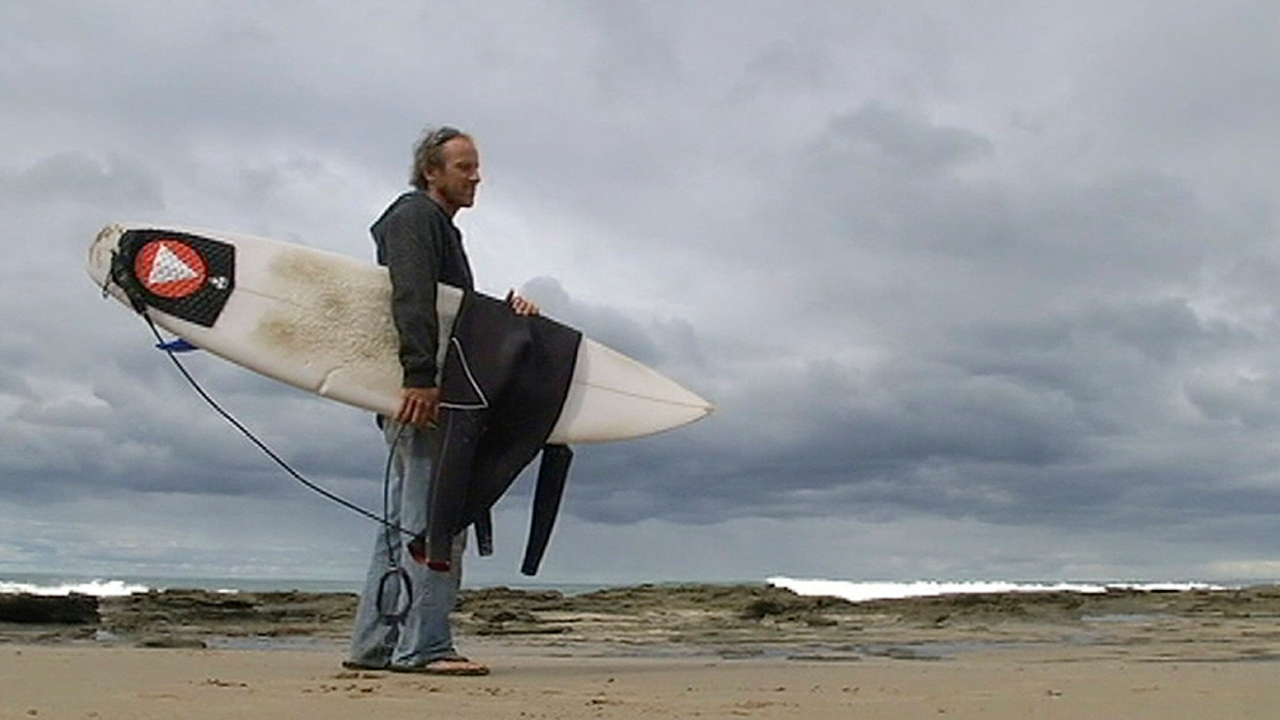 In this photo taken from video, Marcel Brunder, 37, holds his board as he looks out to sea after being attacked while surfing, Tuesday, Aug. 29, 2017, in the waters near Lorne, 140 kms. (90 miles) southwest of Melbourne, Australia. Surviving the attack with a scratch, torn wetsuit and teeth marks on his board, Brundler estimated the shark was a 3-meter (10-foot) great white shark. (Australia Broadcasting Corporation via AP)