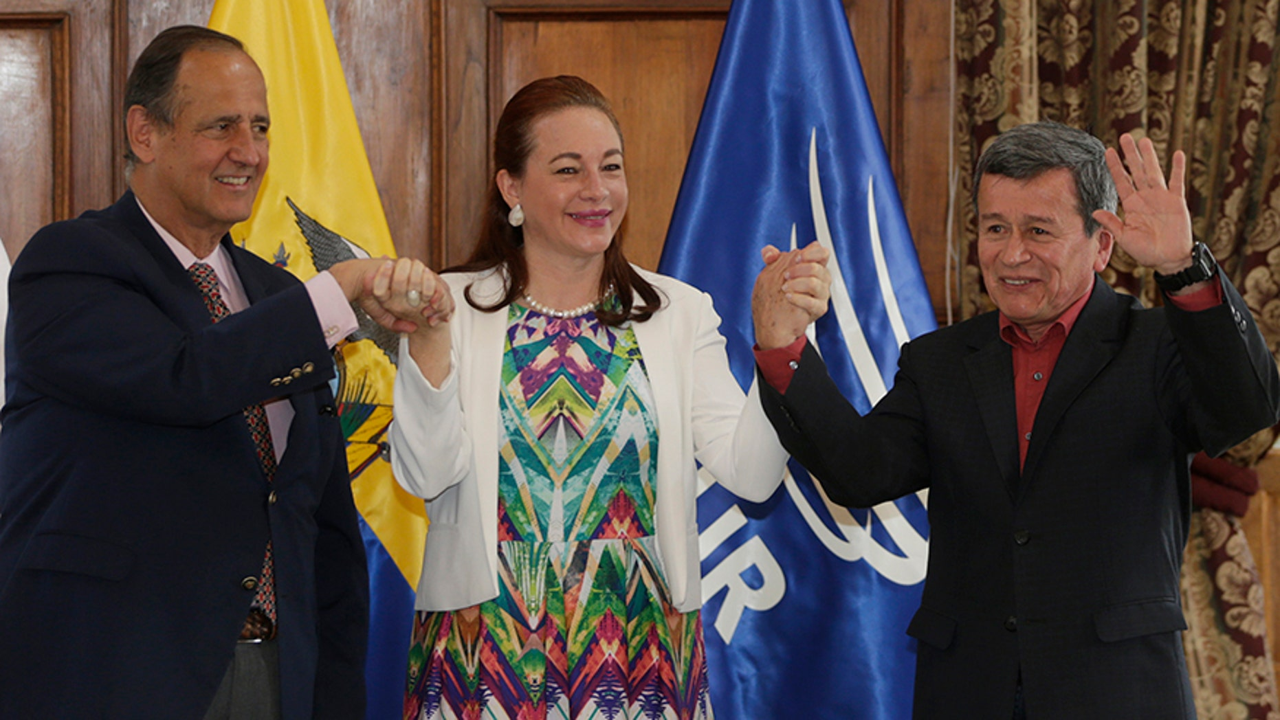 Ecuador's Foreign Minister Fernanda Espinosa stands between ELN rebel leader Pablo Beltran, right, and Colombia's government representative Juan Camilo Restrepo at the end of a press conference announcing the signing of a cease-fire in Quito, Ecuador, Monday, Sept. 4, 2017. Colombia's government and last remaining major rebel group signed a bilateral cease-fire Monday ahead of Pope Francis' visit this week, an agreement seen as a significant step toward negotiating a permanent peace deal. (AP Photo/Dolores Ochoa)