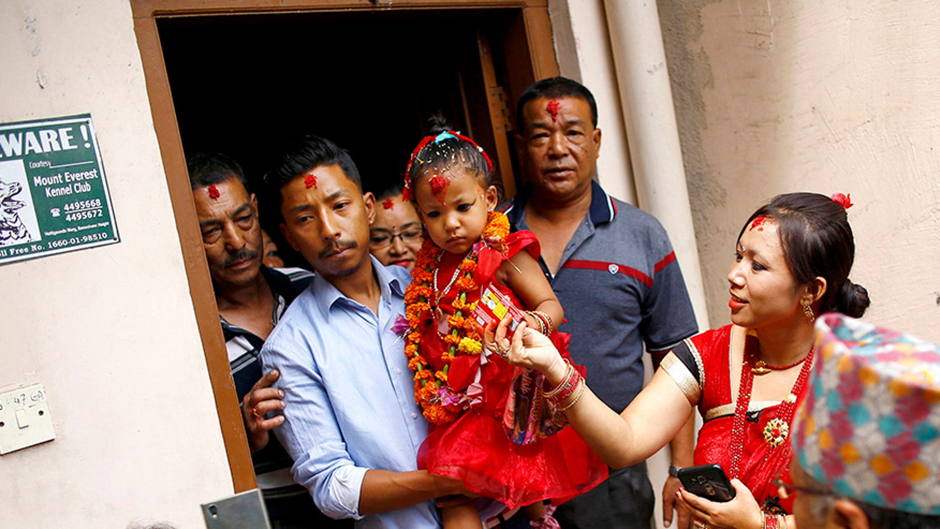 Nepal's new living goddess Trishna Shakya, 3, is carried by her father as they leave home for a temple palace in Kathmandu, Nepal.
