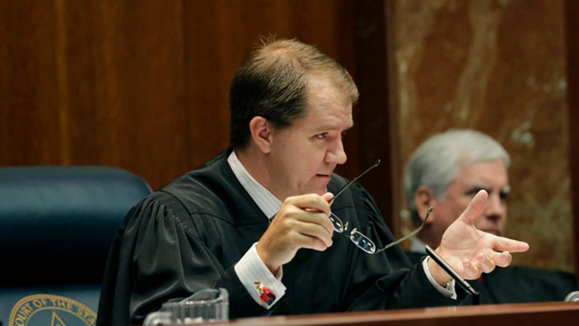 Texas Supreme Court Justice Don Willett, left, asks a question during oral arguments at the state Supreme Court in Austin, Texas.