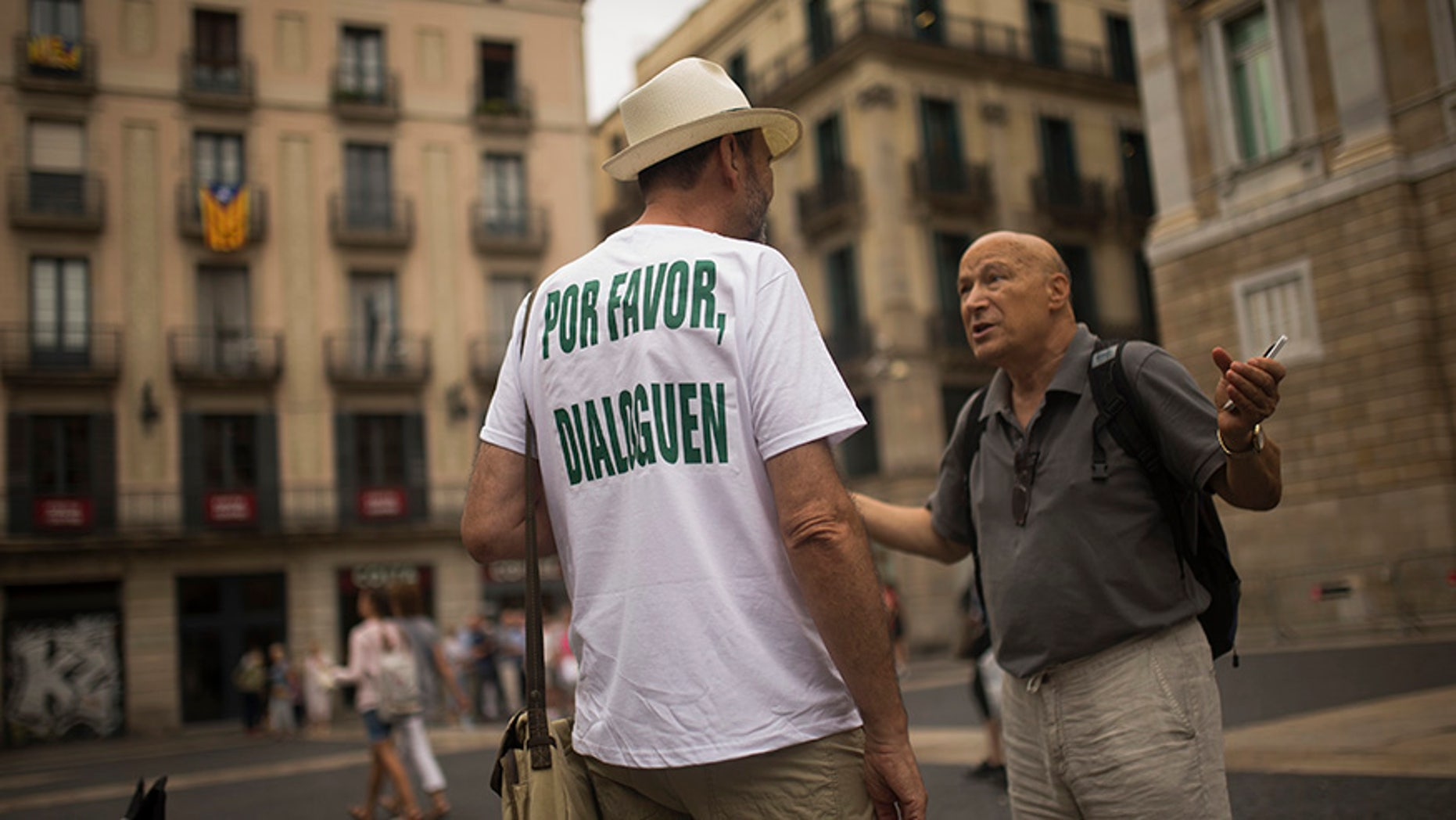 """A man, wearing a t-shirt reading in Spanish: """"Please, talk"""" chats with a passer-by about the current political situation in Catalonia, in Barcelona, Friday, Oct. 6, 2017"""