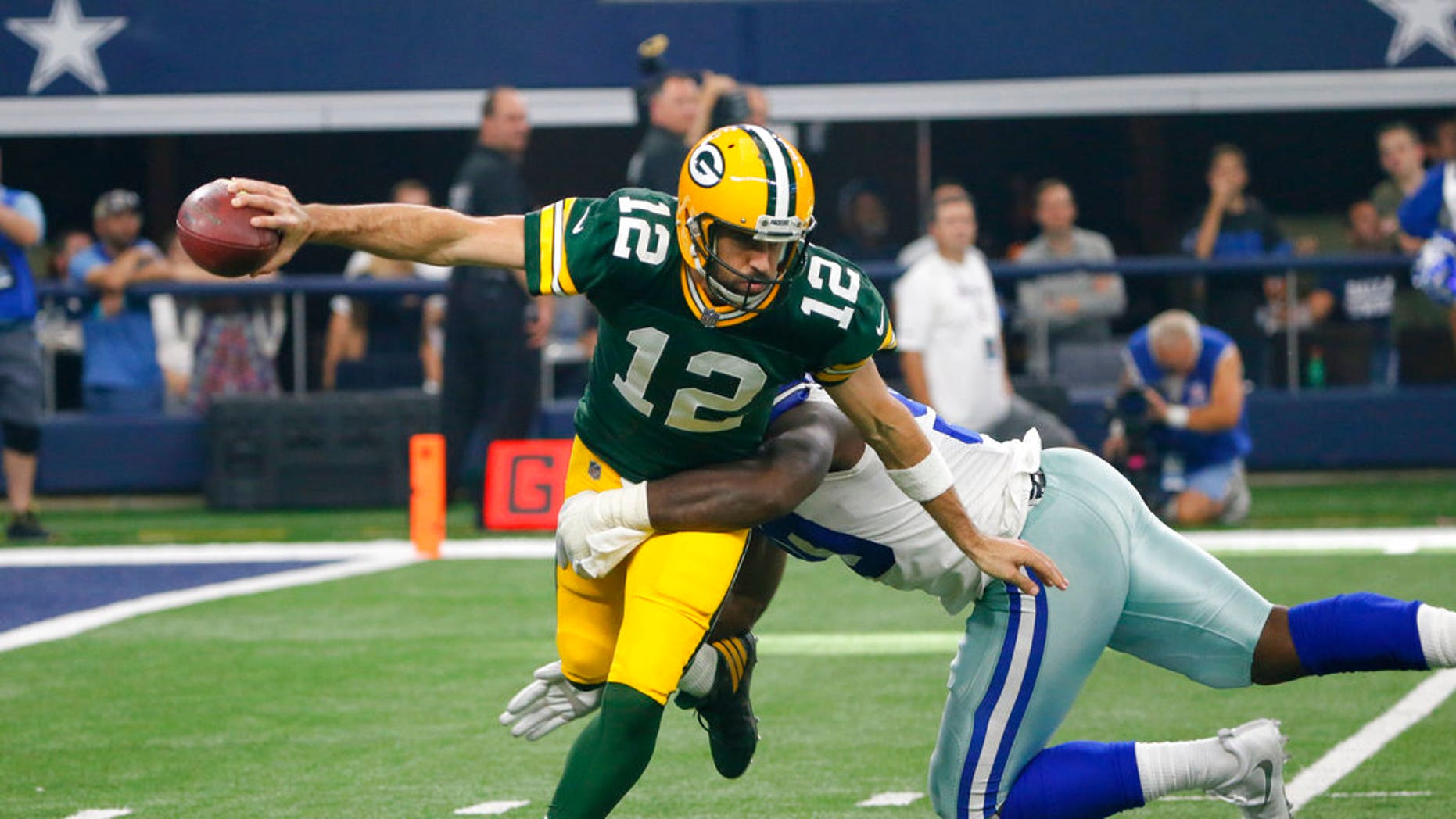 Green Bay Packers quarterback Aaron Rodgers (12) attempts to escape the grasp of Dallas Cowboys defensive end DeMarcus Lawrence (90) before throwing a pass during an NFL football game, Sunday, Oct. 8, 2017, in Arlington, Texas. (AP Photo/Roger Steinman)