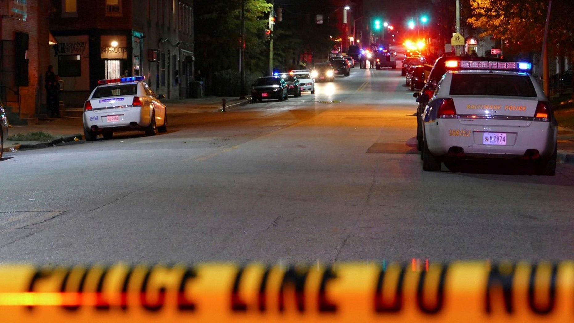 Police officers respond to Bennett Place and N. Fremont Avenue after a call went out that an officer was shot Wednesday in Baltimore, M.D.