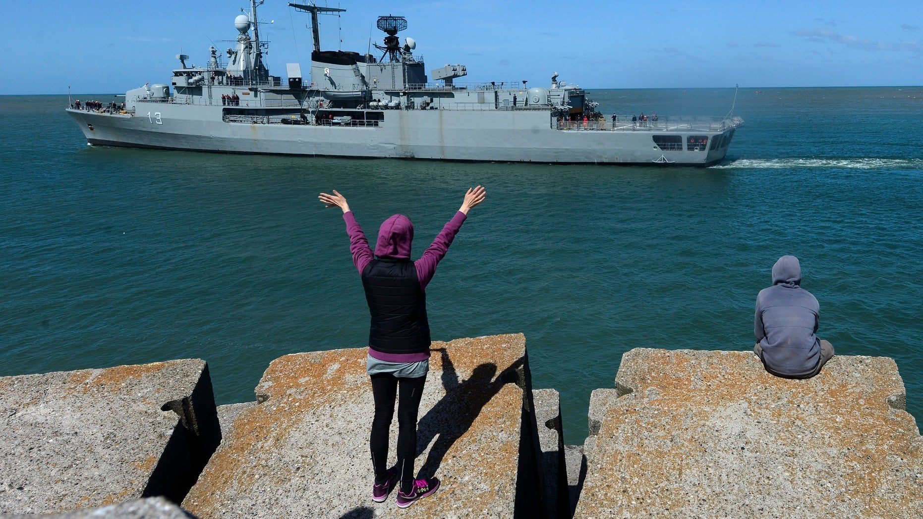 A person waves at the Argentine destroyer Sarandi as it leaves a Navy base in Mar del Plata, Argentina, to participate in the search of the missing submarine, Tuesday, Nov. 21, 2017. The search continues for the missing submarine, with 44 crew members, that has been lost since Nov. 15 in the South Atlantic. (AP Photo/Marina Devo)