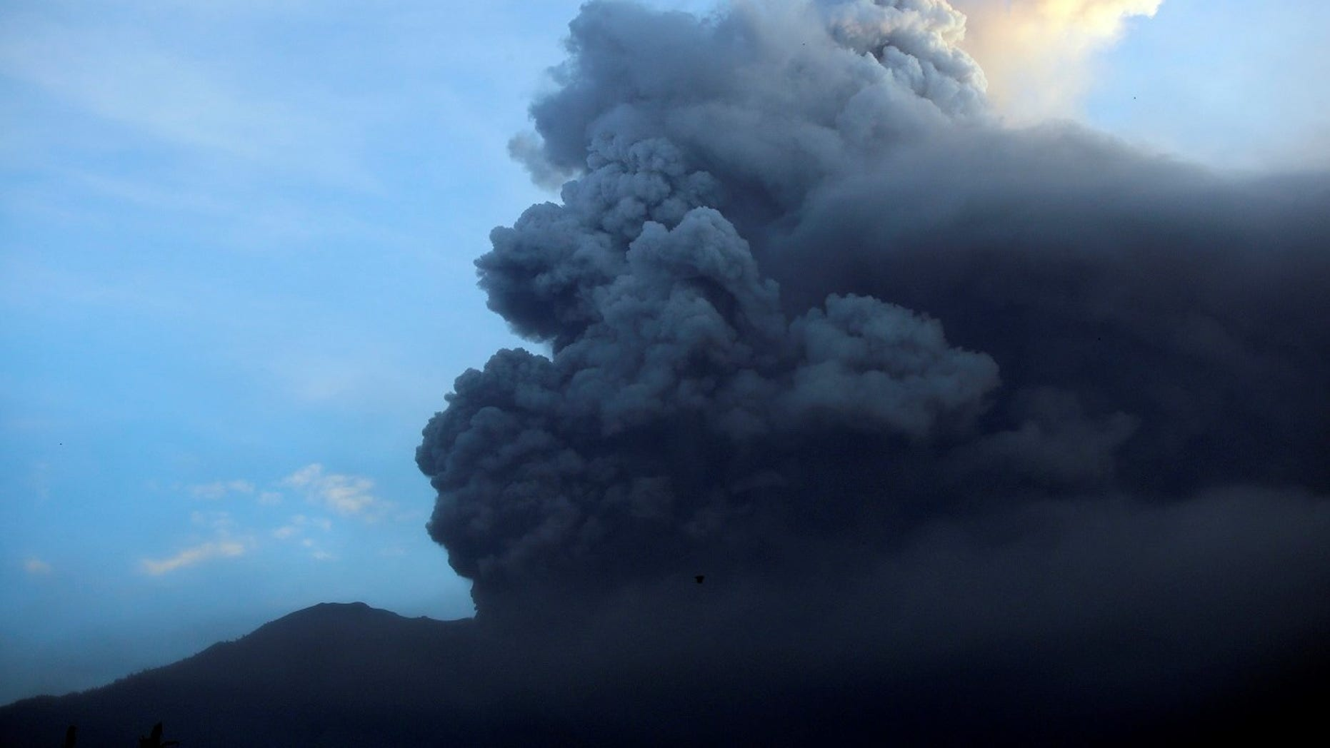 A view of the Mount Agung volcano erupting at sunrise in Karangasem, Bali island, Indonesia, Sunday, Nov. 26, 2017. A volcano on the Indonesian tourist island of Bali erupted for the second time in a week on Saturday, disrupting international flights even as authorities said the island remains safe. (AP Photo/Firdia Lisnawati)