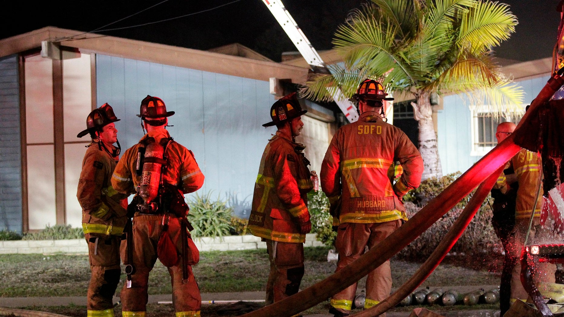 Firefighters gather outside a San Diego house where a small plane crashed, Dec. 9, 2017.