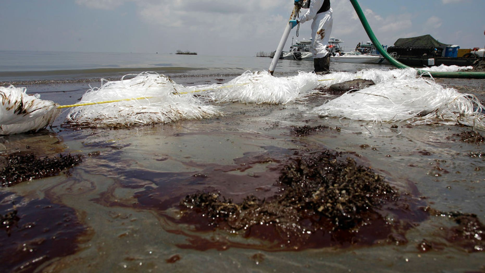 A worker uses a suction hose to remove oil washed ashore from the Deepwater Horizon spill, in Belle Terre, La., June 9, 2010.
