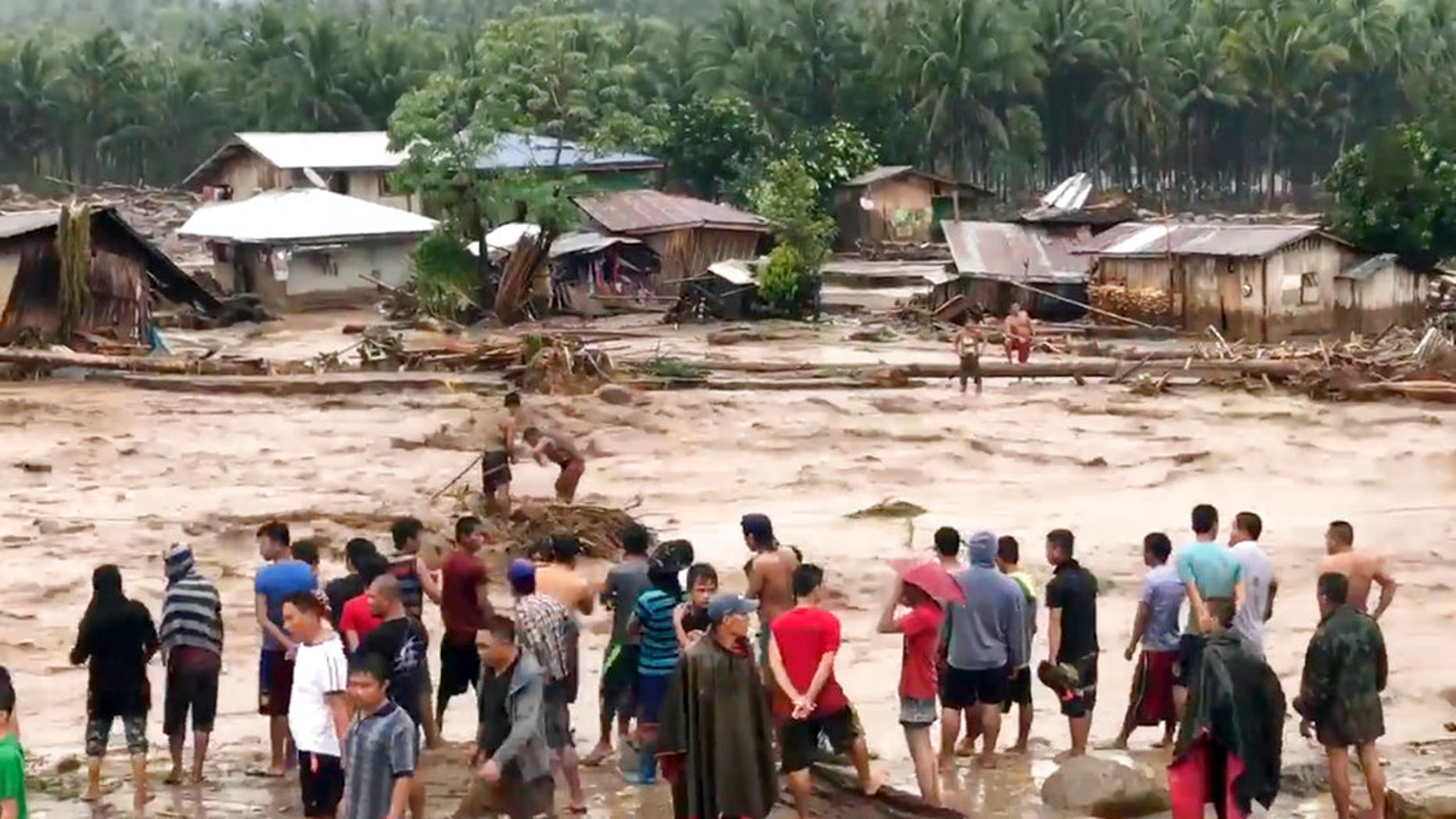 In this photo made from video by Aclimah Disumala, Friday, Dec. 22, 2017, villagers carry cross raging flood waters in Lanao del Norte, Zamboanga Pennisula, southern Philippines. A tropical storm has unleashed flash floods and set off landslides in the southern Philippines leaving dozens of people dead. (Aclimah Disumala via the AP)