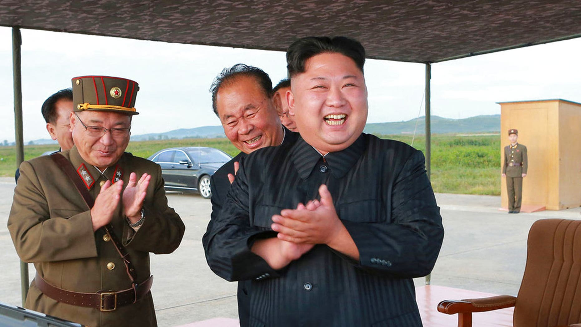 North Korean leader Kim Jong Un celebrates what was said to be the test launch of a Hwasong-12 missile, in an undated government photo that was distributed Sept. 16, 2017.