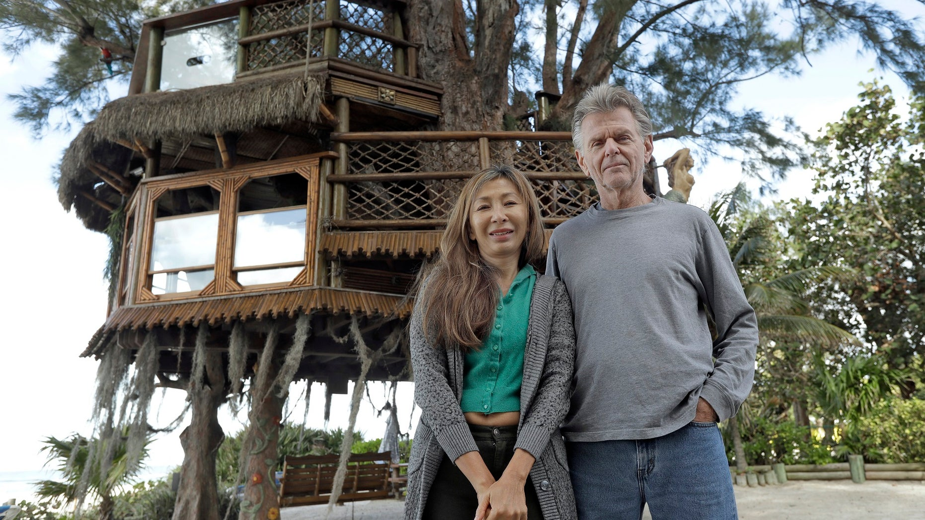 Lynn Tran and her husband, Richard Hazen, near their Australian pine treehouse on Thursday in Holmes Beach, Fla. The couple hope the U.S. Supreme Court will hear their case after city and state officials ordered the treehouse removed.