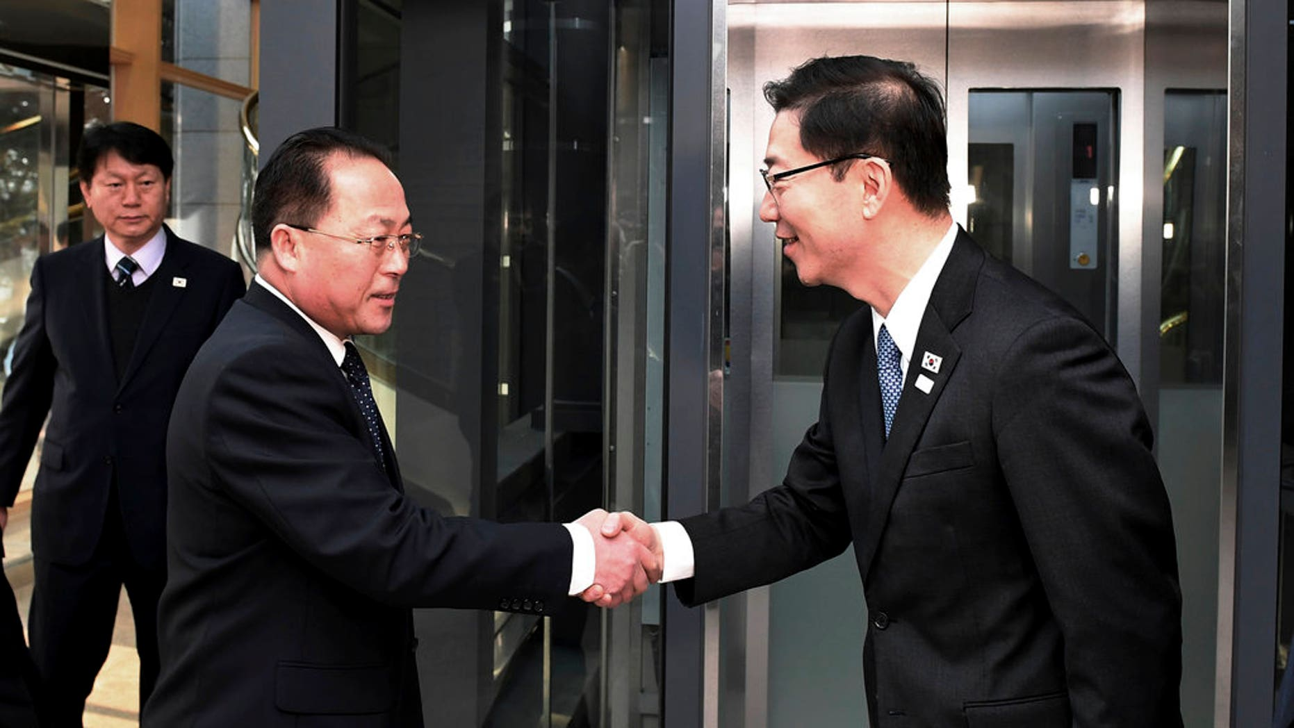 South Korean Vice Unification Minister Chun Hae-sung, right, shakes hands with the head of North Korean delegation Jon Jong Su before a meeting to discuss Olympics cooperation.