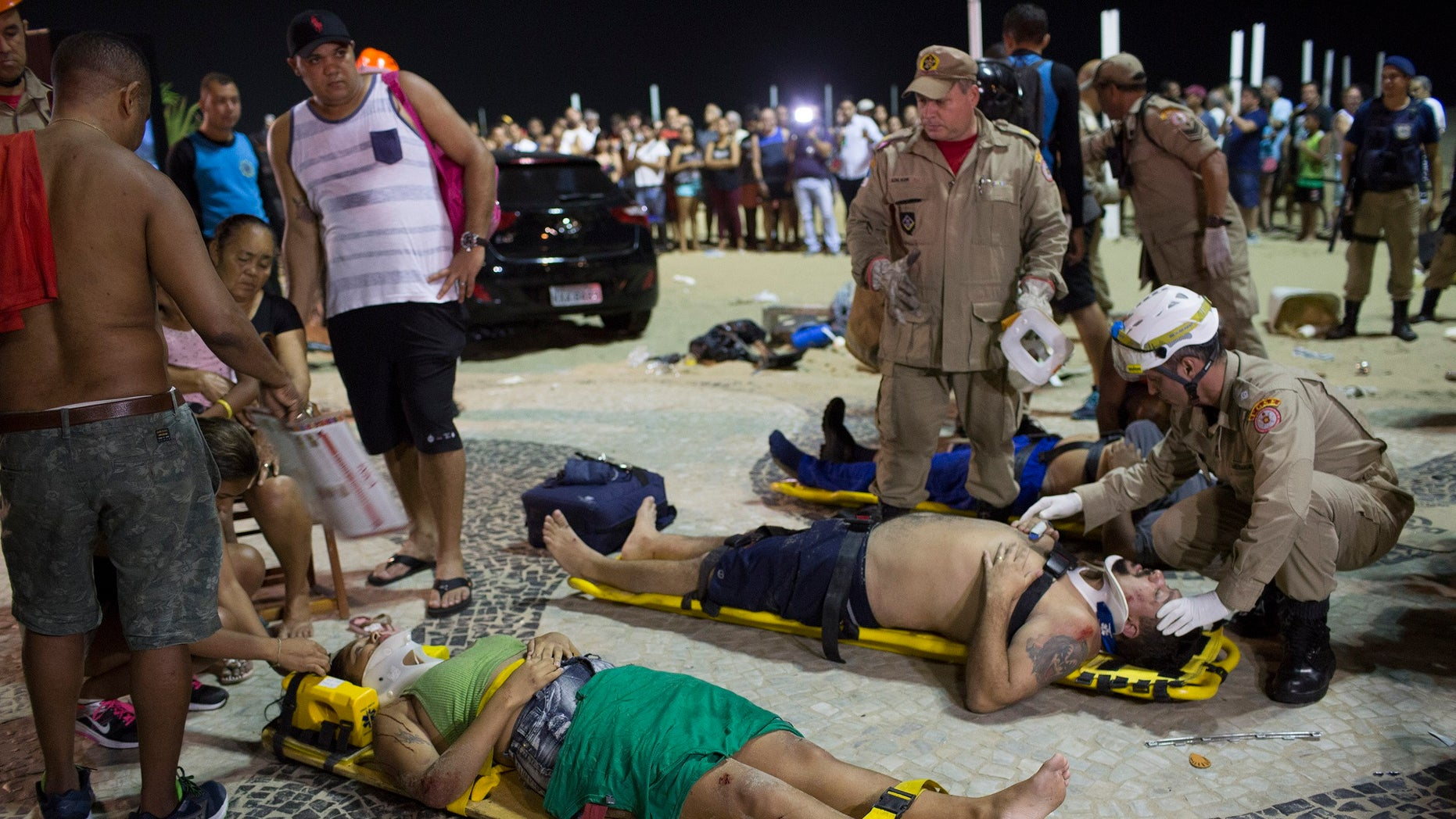 Firefighters provide aid to people that were injured when a car drove into the crowded seaside boardwalk along Copacabana beach in Rio de Janeiro, Brazil on Thursday.