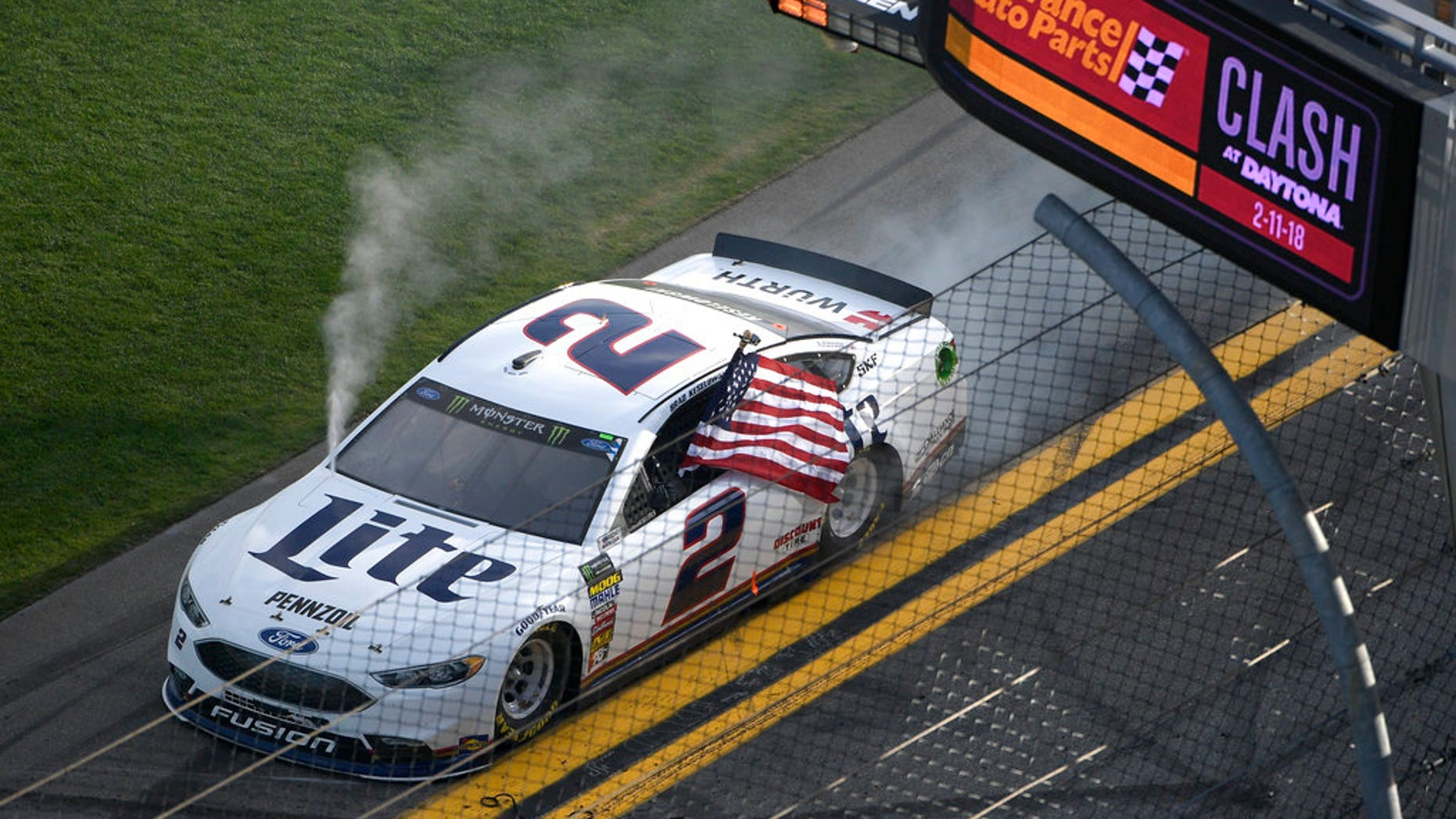 Brad Keselowski (2) carries a United States flag past the finish line after winning the NASCAR Clash auto race at Daytona International Speedway Sunday, Feb. 11, 2018, in Daytona Beach, Fla. (AP Photo/Phelan M. Ebenhack)