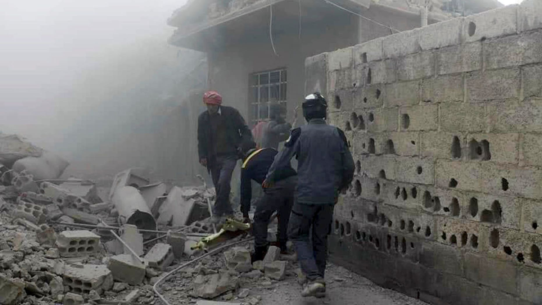 Members of the Syrian Civil Defense group and civilians gathered to help survivors from a street attacked by airstrikes and shelling by Syrian government forces in Ghouta, a suburb of Damascus, Syria.