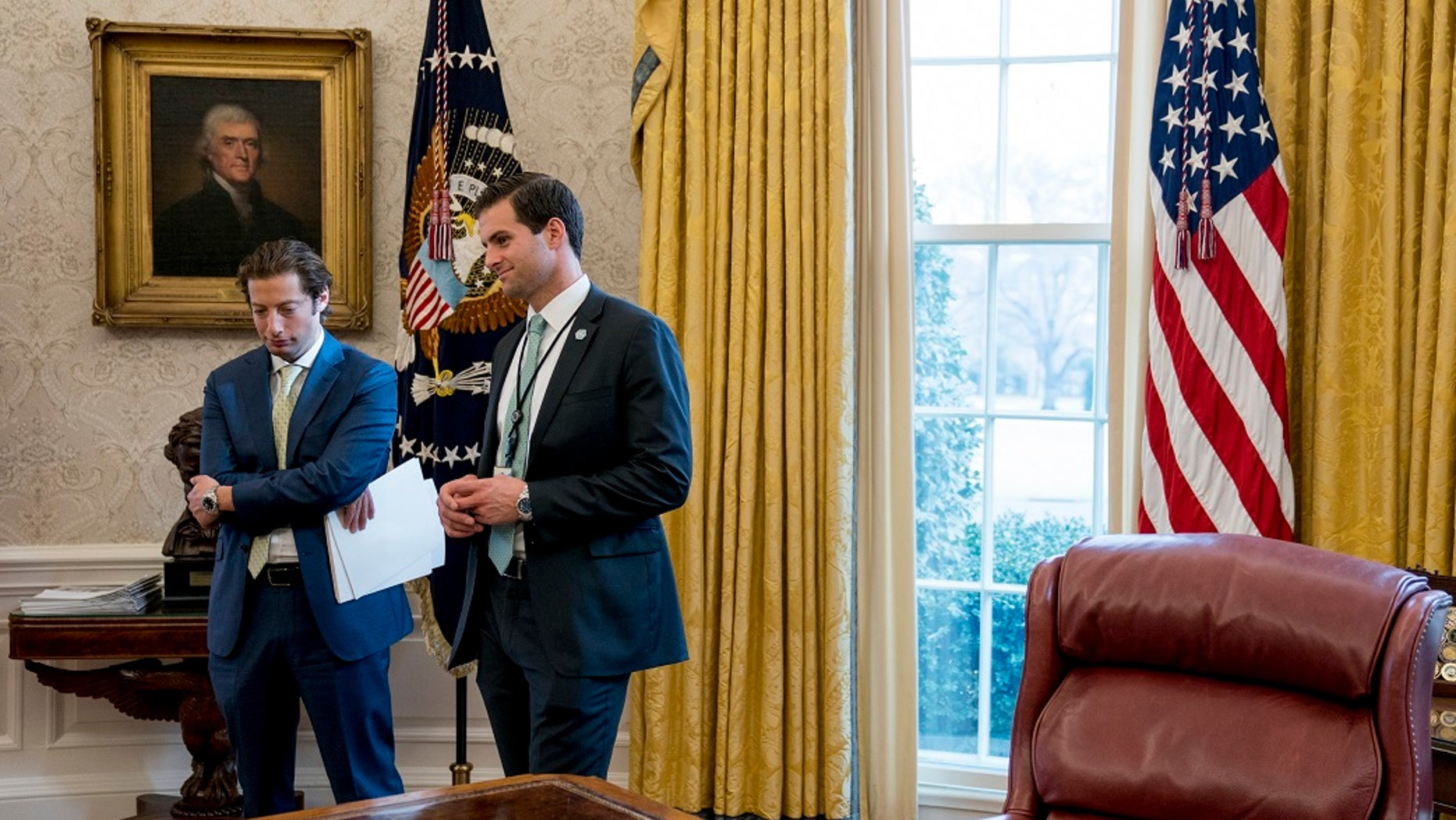 White House aide John McEntee, right, and Treasury Secretary Steve Mnuchin's Chief of Staff Eli Miller, left, stand in the Oval Office as President Donald Trump speaks at a tax reform meeting with American workers at the White House in Washington. Trump's personal aide is leaving the White House and will rejoin his campaign.