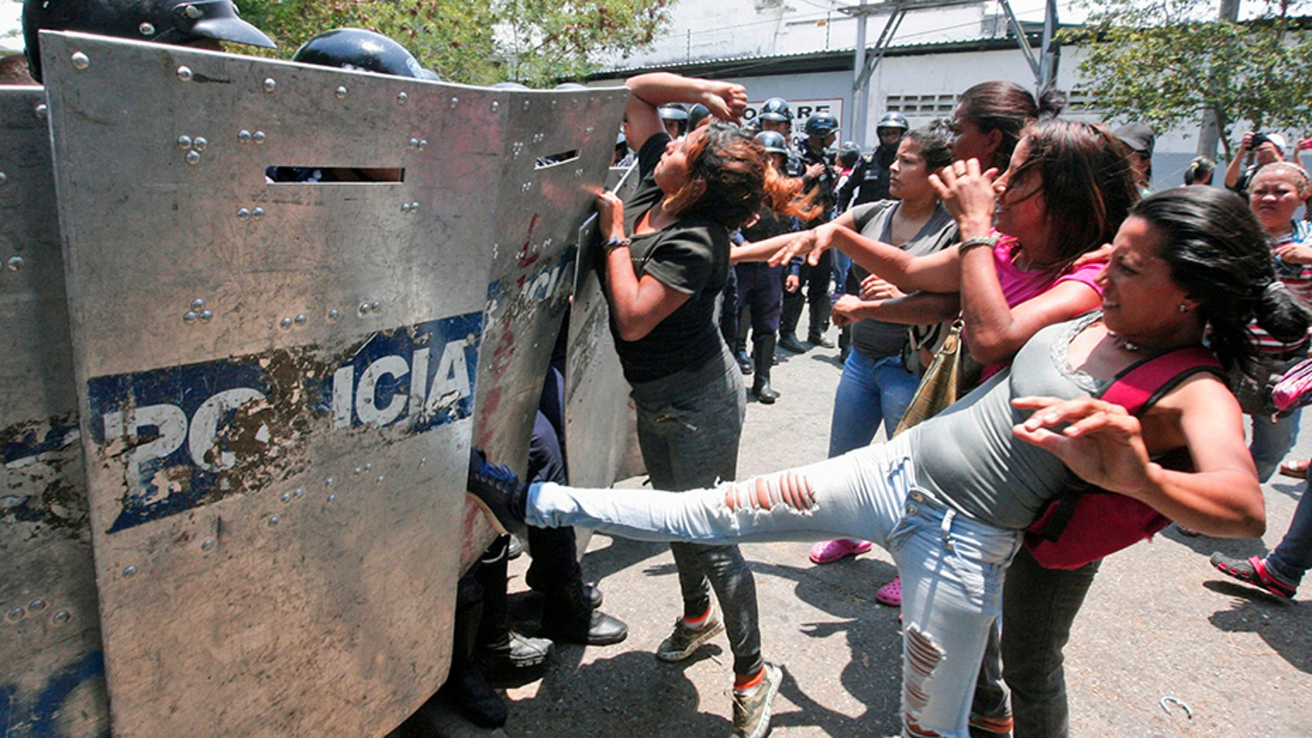 A woman kicks at a riot police shield as relatives of prisoners wait to hear news about their family members imprisoned at a police station where a riot broke out, in Valencia, Venezuela.