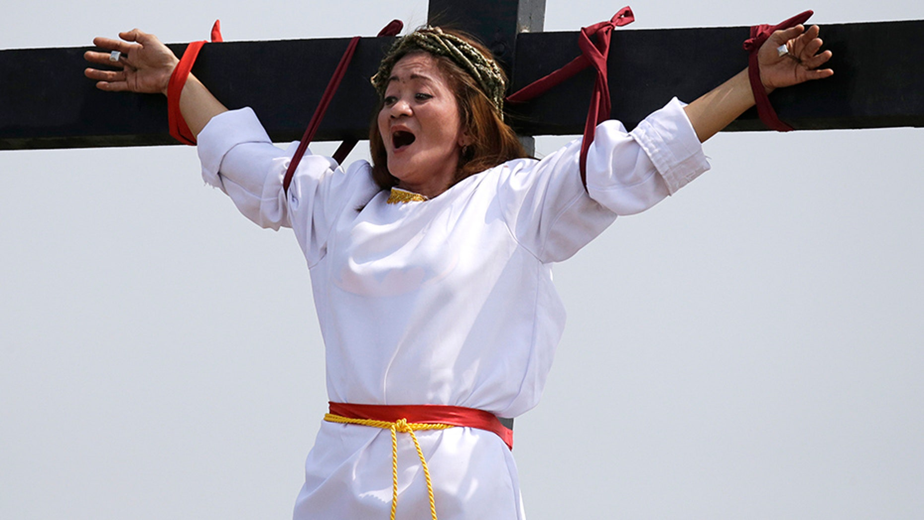 Maryjane Sazon, a 39-year-old beauty salon worker, grimaces as she gets nailed to the cross as part of Good Friday rituals in the village of San Pedro Cutud, Pampanga province, northern Philippines.