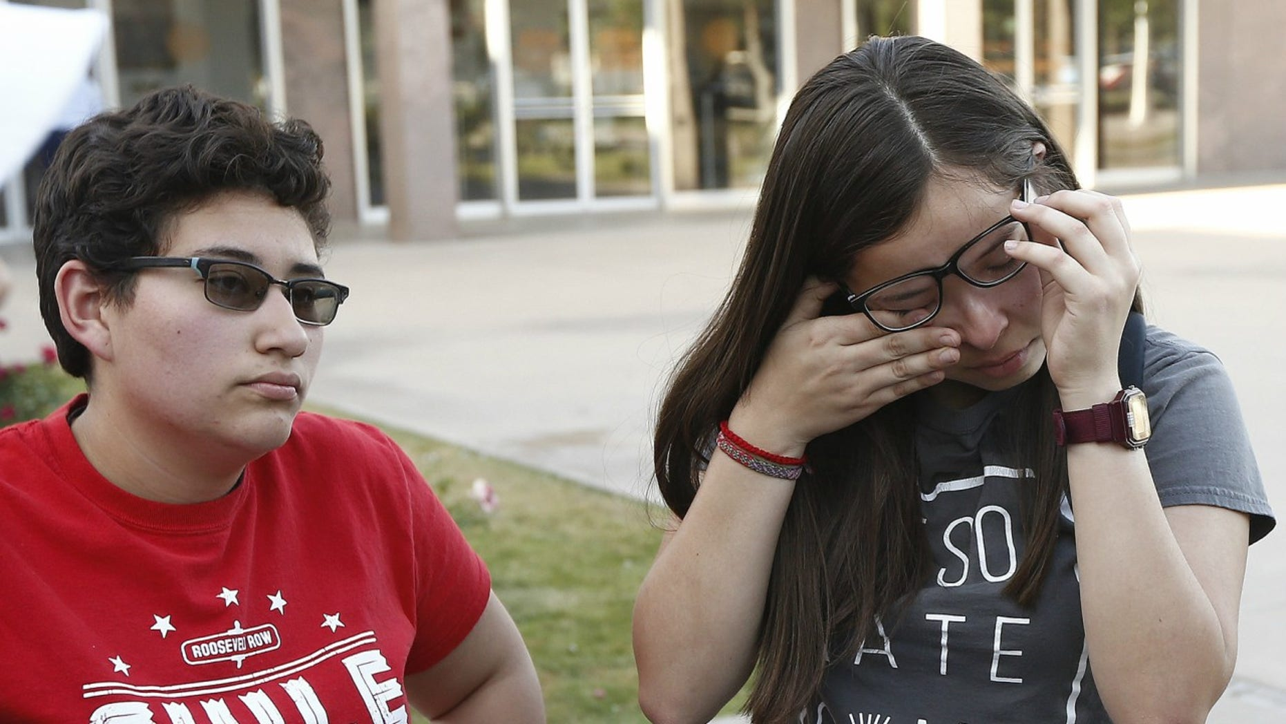 Darian Cruz, right, wipes away tears as she and Jasmin Lopez, left, listen to a friend talk about the Arizona Supreme Court ruling against young immigrants granted deferred deportation status under the 2012 Deferred Action for Childhood Arrivals program, during a demonstration at the Arizona Capitol in Phoenix, April 9, 2018.