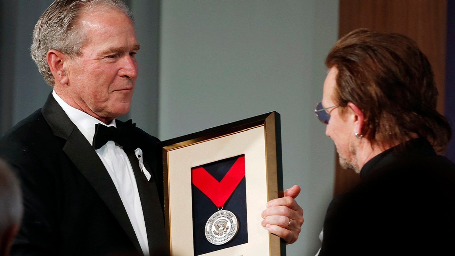 Former President George W. Bush, left, presents a medal of Distinguished Leadership to U2 musician Bono during a gala for the Forum on Leadership at the George W. Bush Institute, Thursday, April 19, 2018, in Dallas.