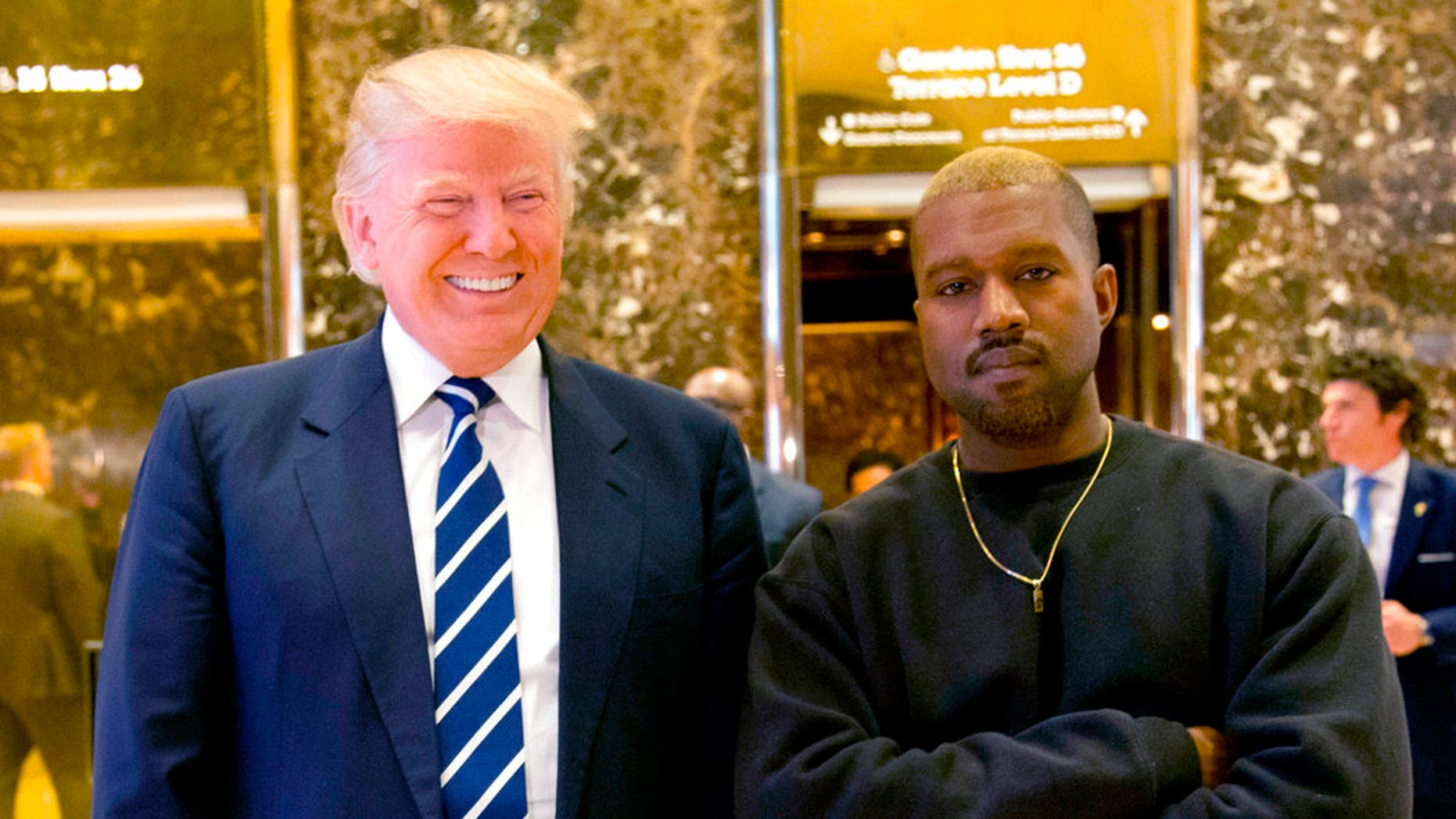Then-President-elect Donald Trump and Kanye West pose for a photo in the lobby of Trump Tower in New York City, Dec. 13, 2016.