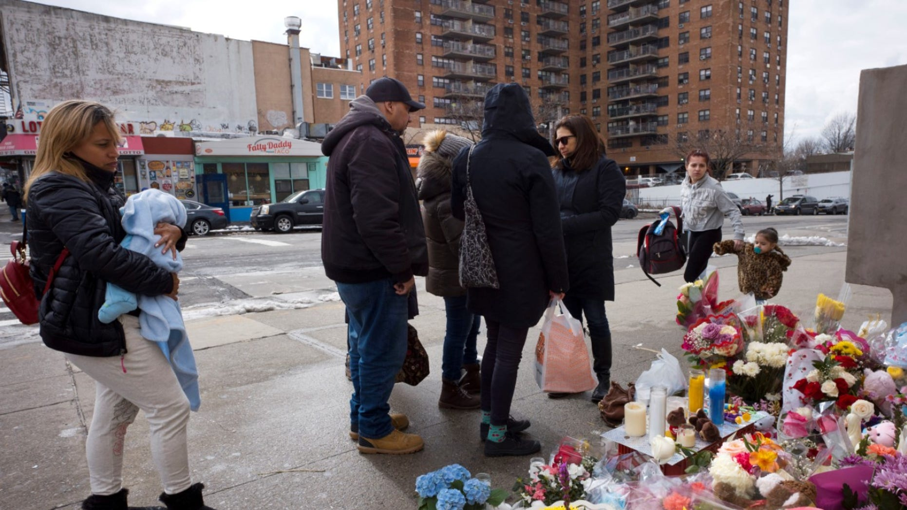 People gather at a sidewalk memorial for two children who were killed in March when they were struck by a car driven by a woman who likely had a seizure behind the wheel, in the Park Slope neighborhood of the Brooklyn borough of New York. The driver, Dorothy Bruns, was arrested at her Staten Island home on Thursday, May 3, and has been charged with manslaughter.