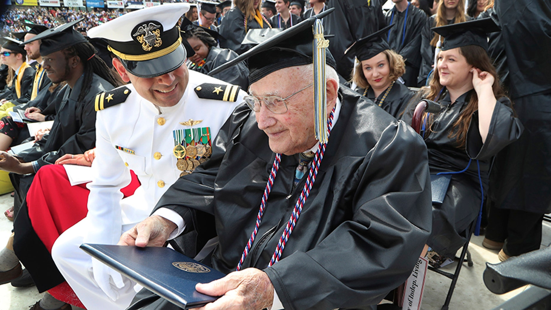 World War II veteran Bob Barger, assisted by Haraz Ghanbari, University of Toledo director of military and veteran affairs, left, smiles after receiving his diploma at the university's commencement ceremony on Saturday in Toledo, Ohio.