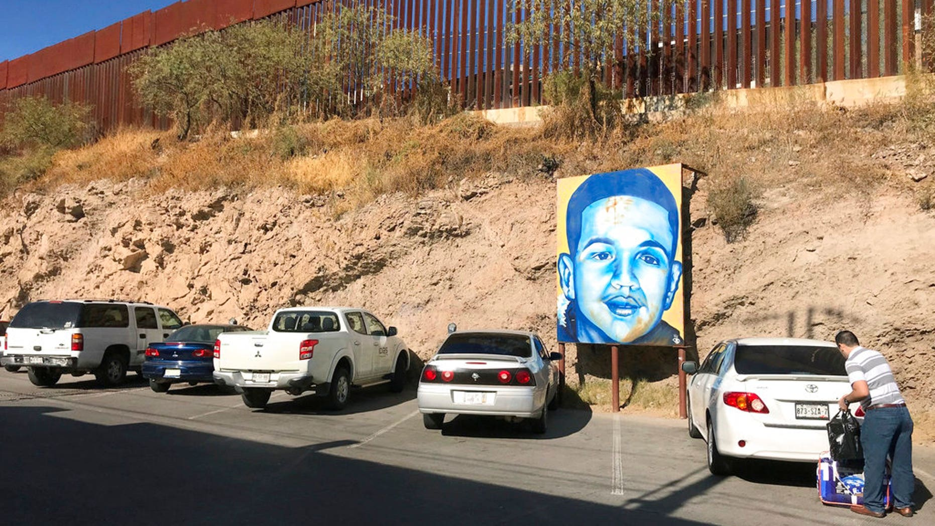 A portrait of Mexican youth Jose Antonio Elena Rodriguez, who was fatally shot in 2012, is displayed along the street where he died, in December 2017.