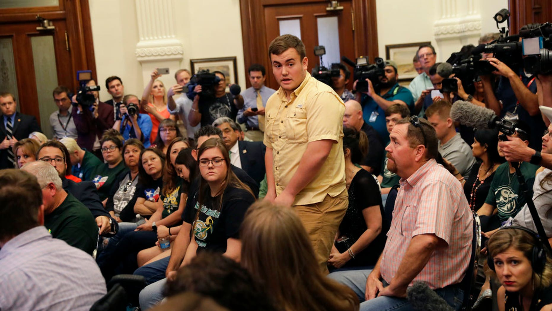 Tyler Morrison, center, a student at Santa Fe High School in Santa Fe, Texas, speaks during a roundtable discussion on gun violence, in Austin, Texas, May 24, 2018.