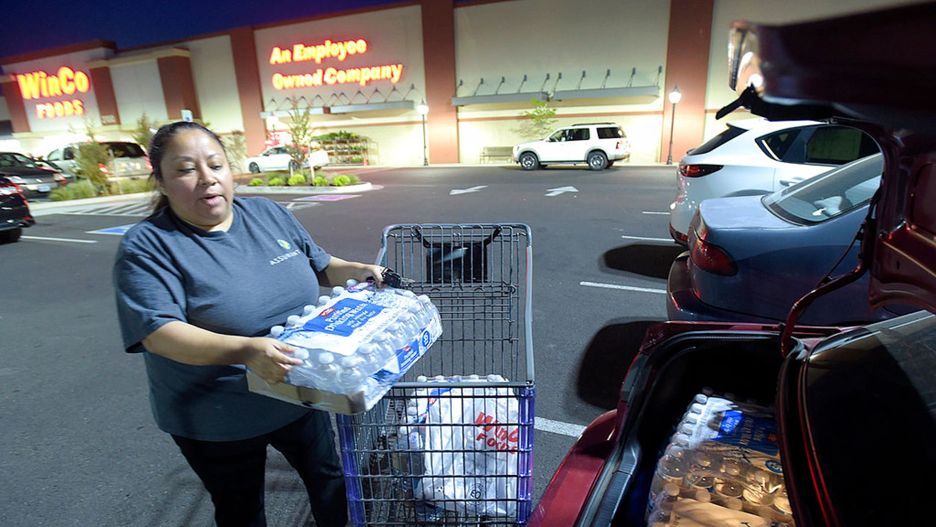 Juana Francisco of Albany, Ore., loads her trunk with water purchased at WinCo, May 29, 2018.