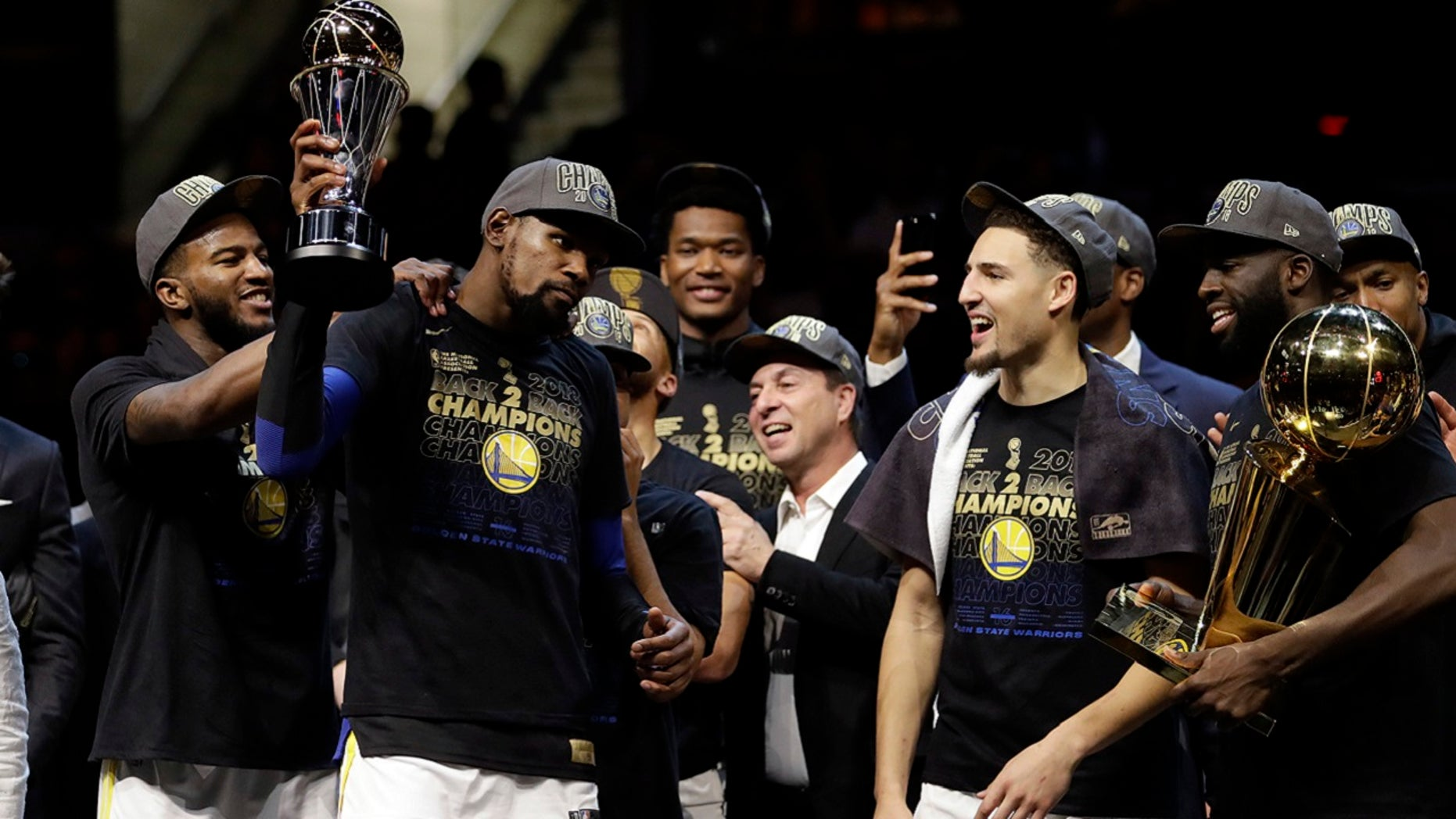 Golden State Warriors' Kevin Durant, second from left, celebrates after the Warriors defeated the Cleveland Cavaliers 108-85 in Game 4 of basketball's NBA Finals to win the NBA championship, Friday, June 8, 2018, in Cleveland.