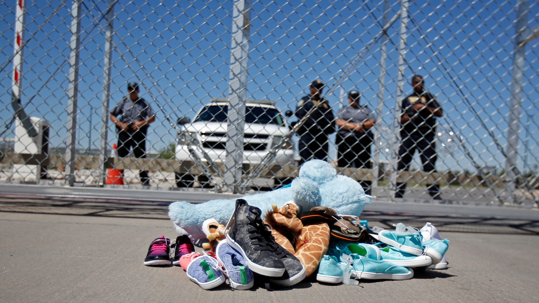 Shoes and a teddy bear, brought by a group of U.S. mayors, are piled up outside a holding facility for immigrant children in Tornillo, Texas, near the Mexican border, Thursday, June 21, 2018.